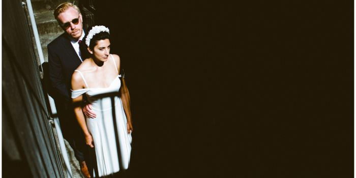 A DIY wedding at Vancouver Rowing Club, bride and groom stand in dramatic light, creative wedding photos