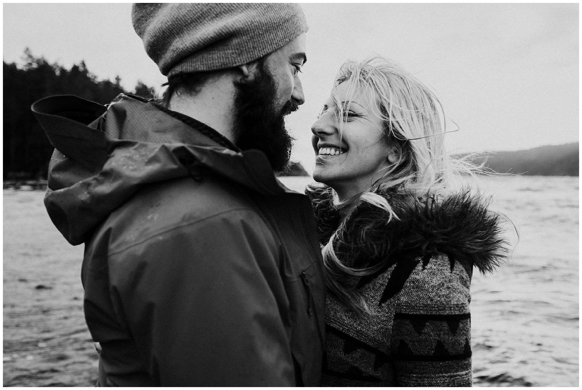 black and white photo of couple laughing on boat during Secret Cove engagement session
