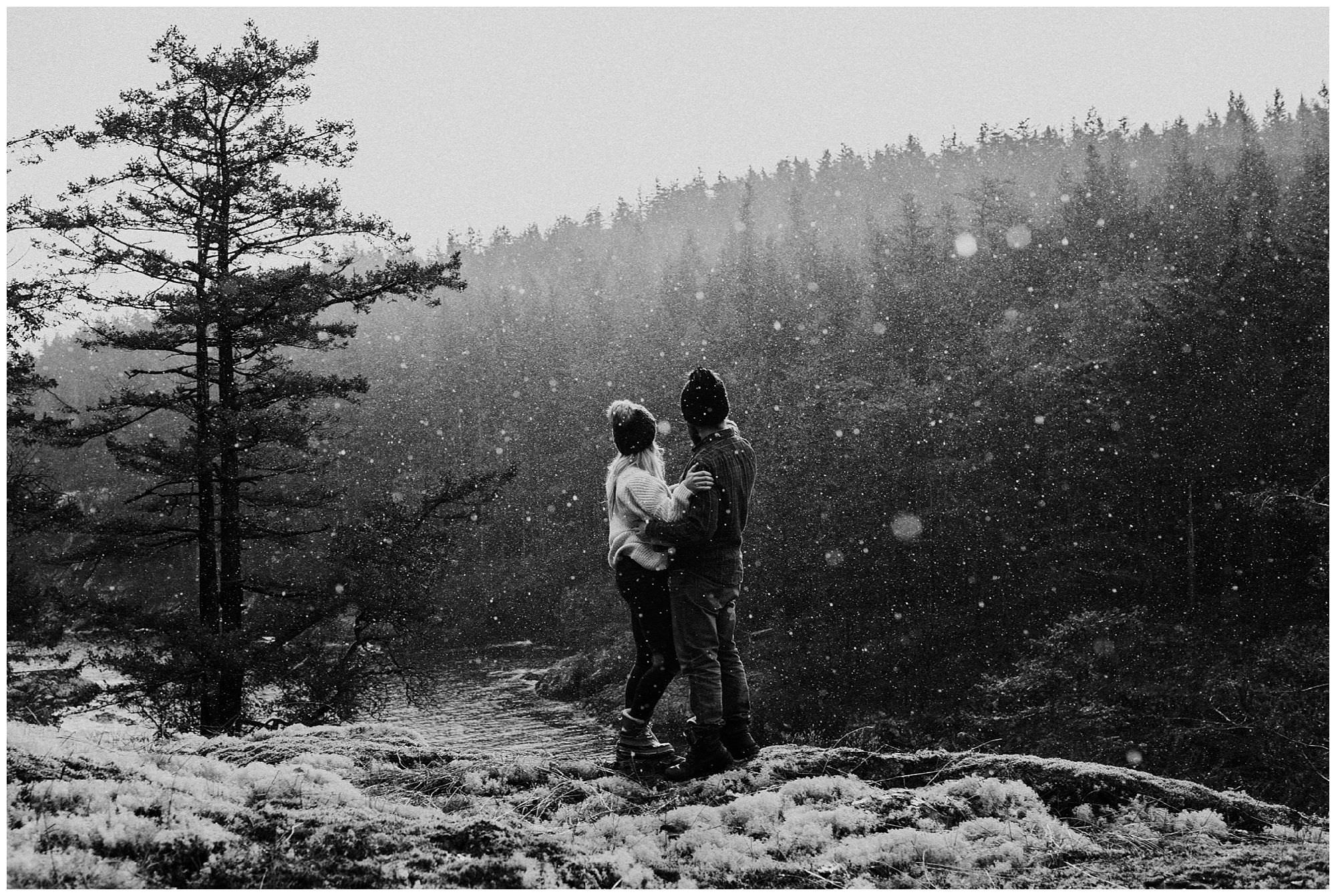 black and white photo of couple standing in backlit rain overlooking Secret Cove