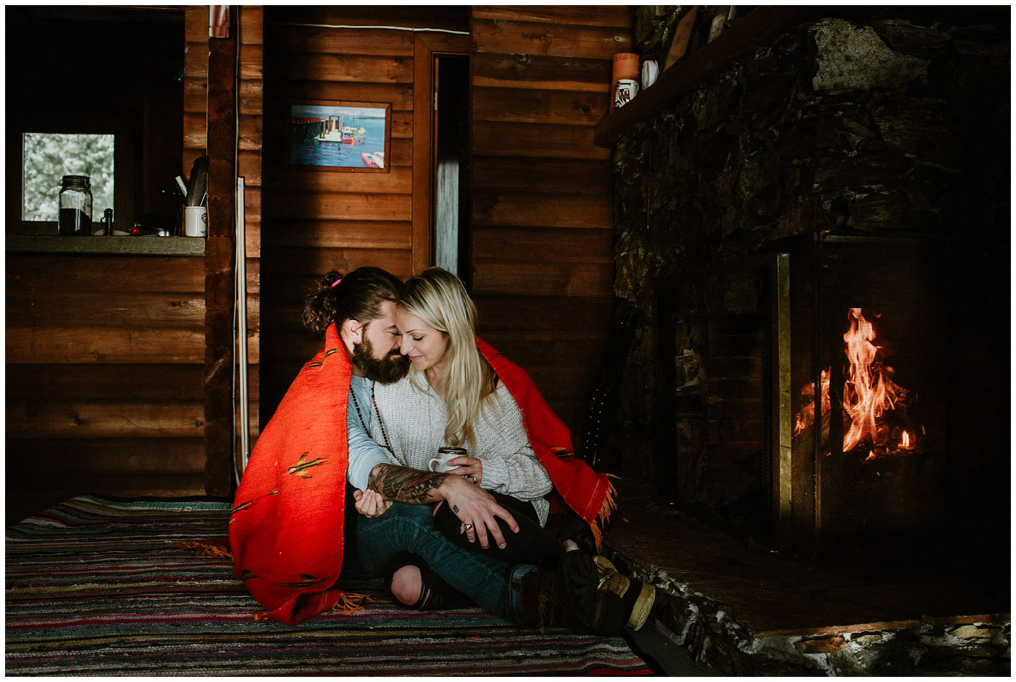 couple cuddling in front of fire in rustic cabin on Thormanby Island