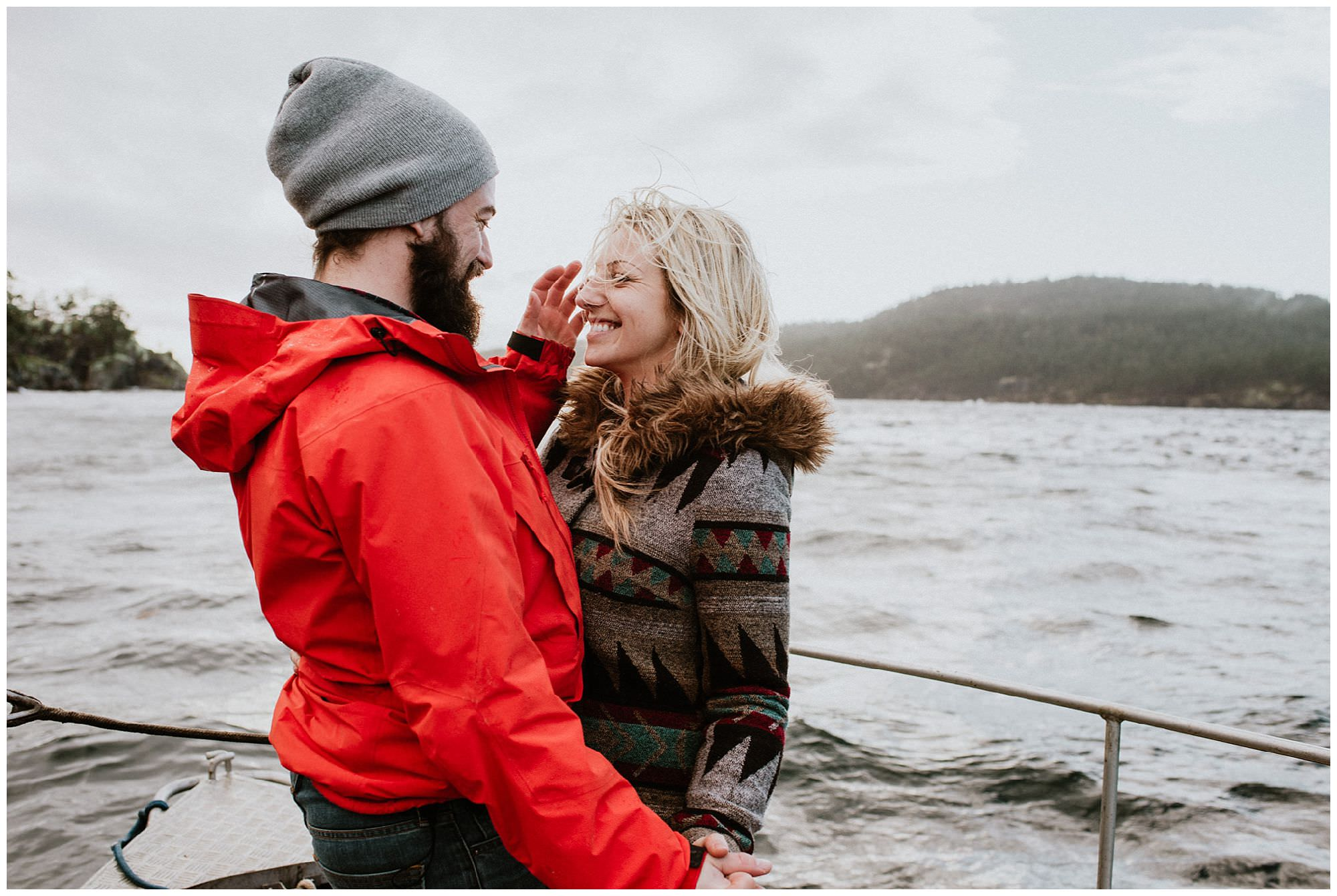 couple in coats standing on boat during Secret Cove engagement session