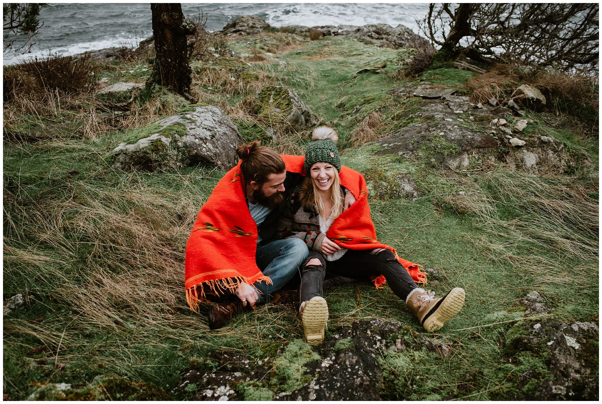 couple laughing in grass in orange blanket on Thormanby Island