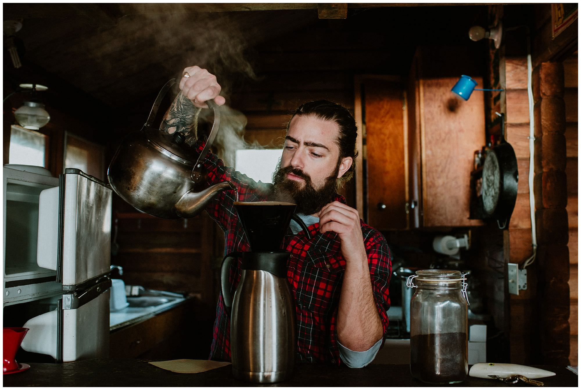 guy with man bun pouring coffee in rustic cabin on Thormanby Island