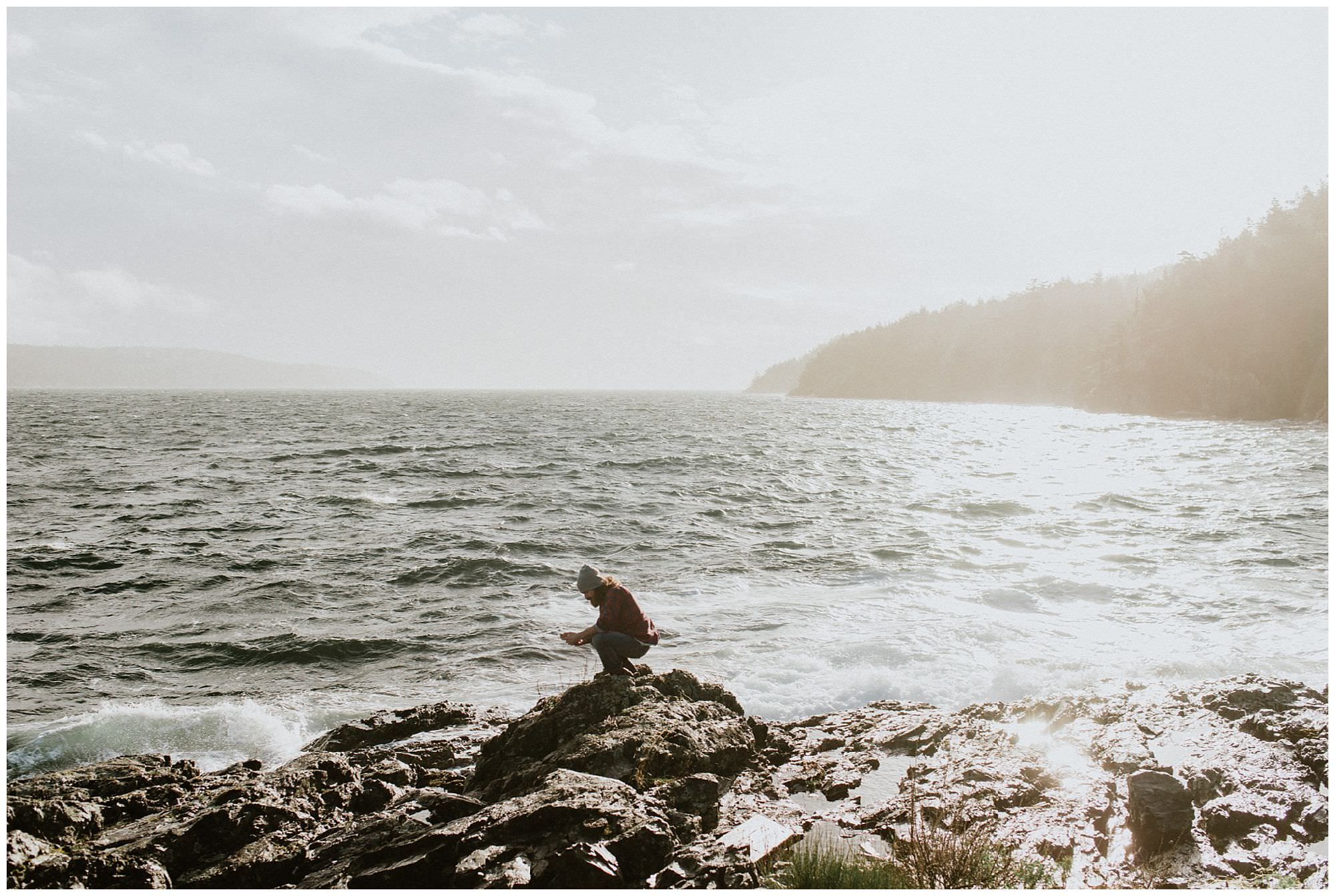 man looking for shells on beach on Thormanby Island engagement session