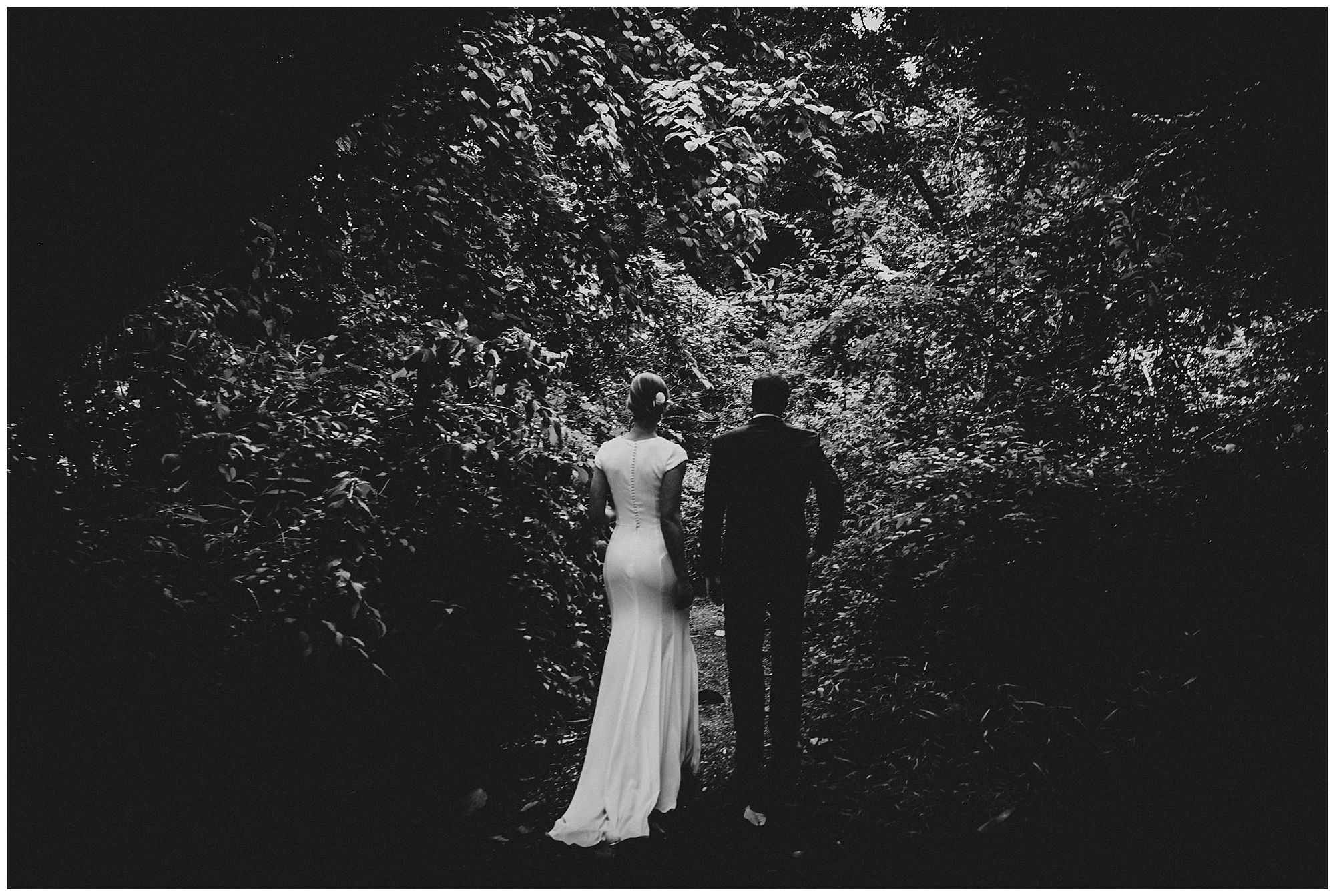 bride and groom walking through forest at UBC Botanical Gardens