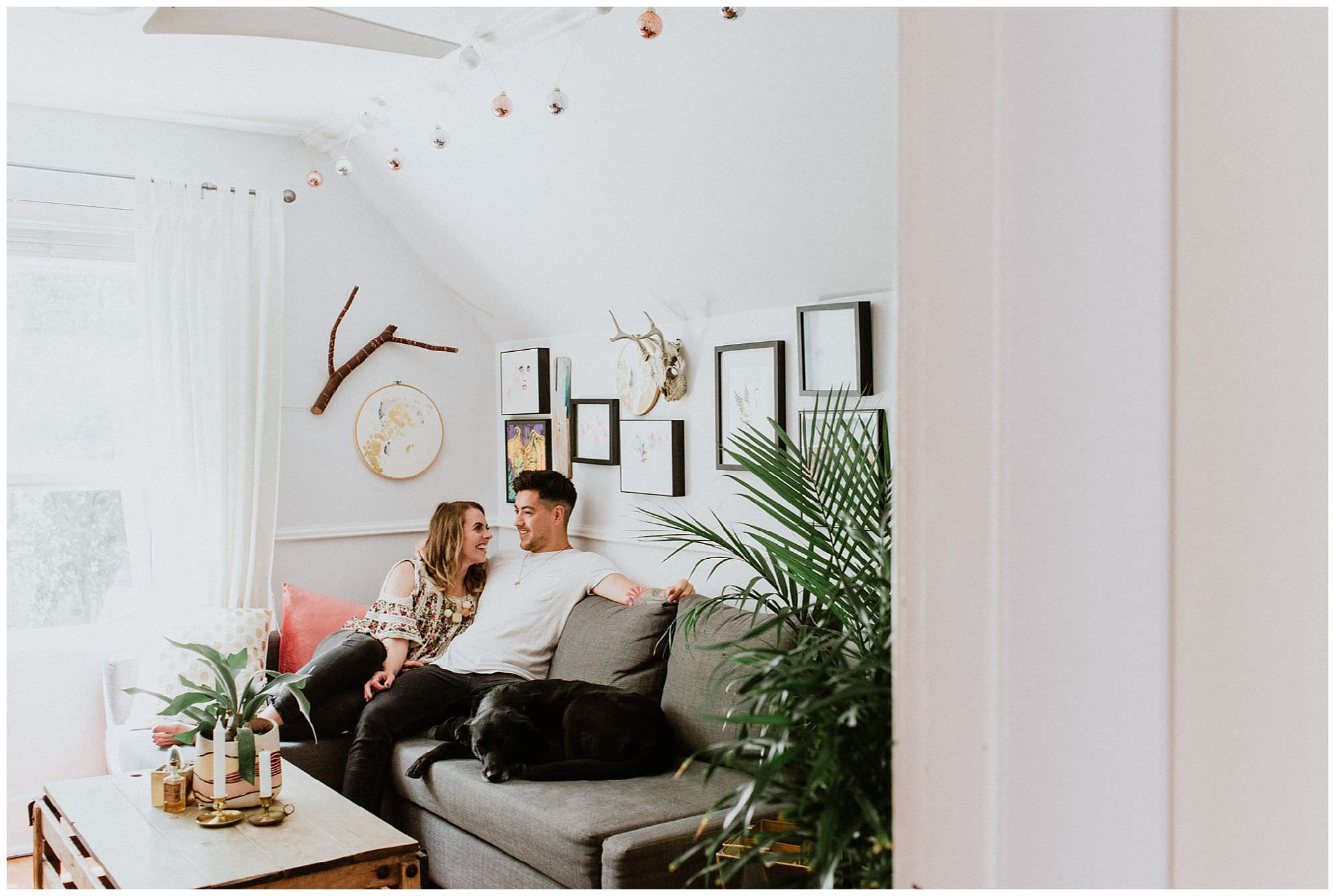 couple cuddling on couch in vintage chic living room in east ...