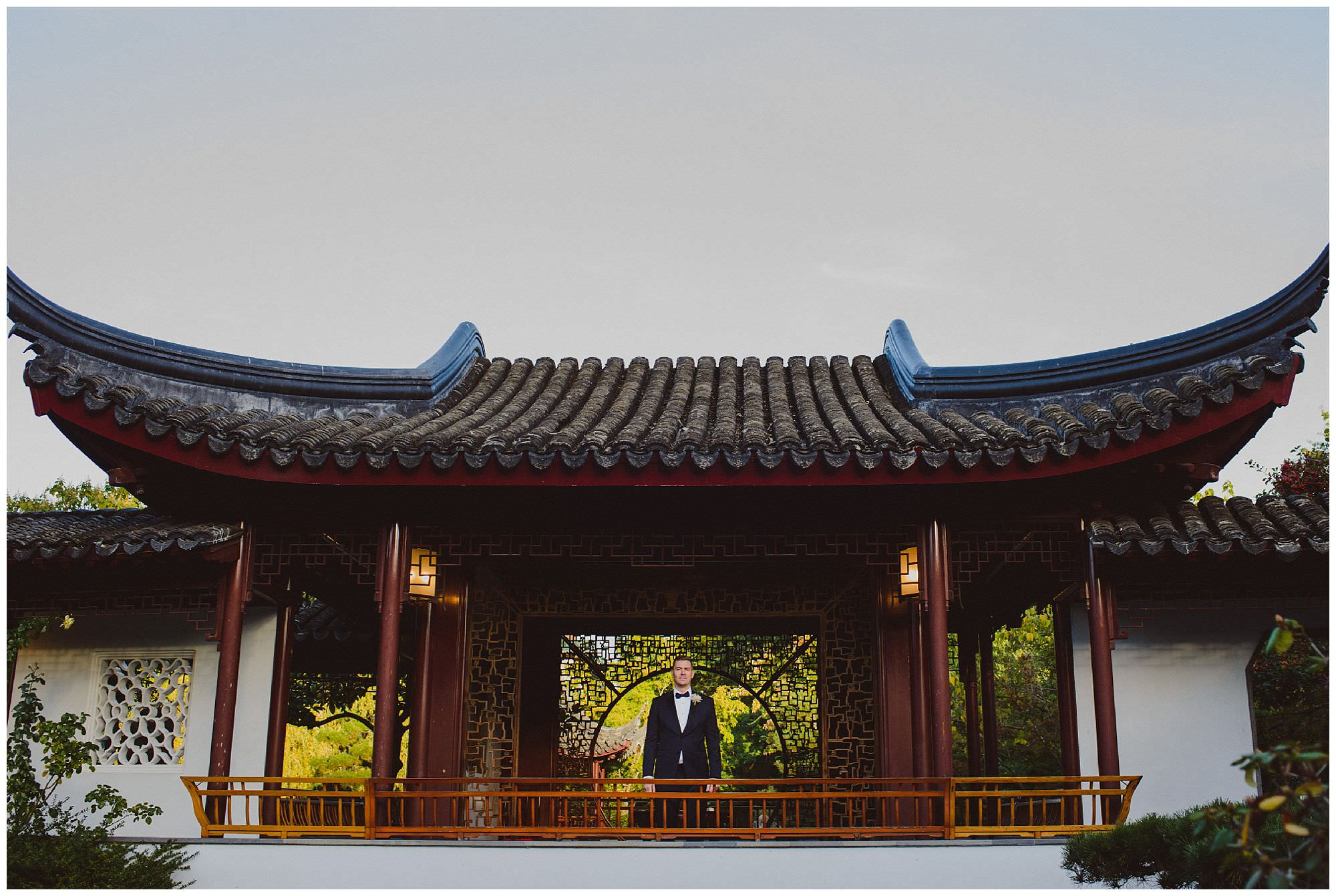 Groom in classic black tie suit stands in Dr. Sun Yat-Sen Classical Chinese Gardens after his intimate wedding, Vancouver wedding photographer