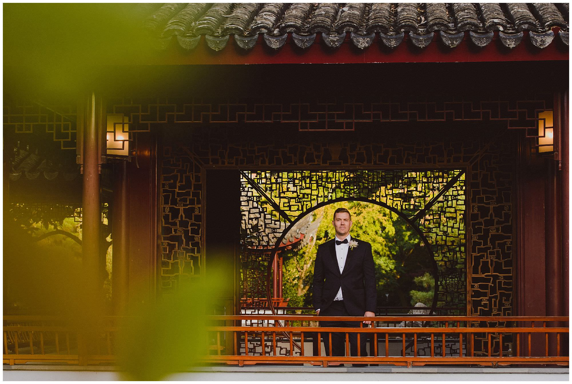 Groom in classic black tie suit stands in Dr. Sun Yat-Sen Classical Chinese Gardens at sunset after his intimate wedding, Vancouver wedding photographer
