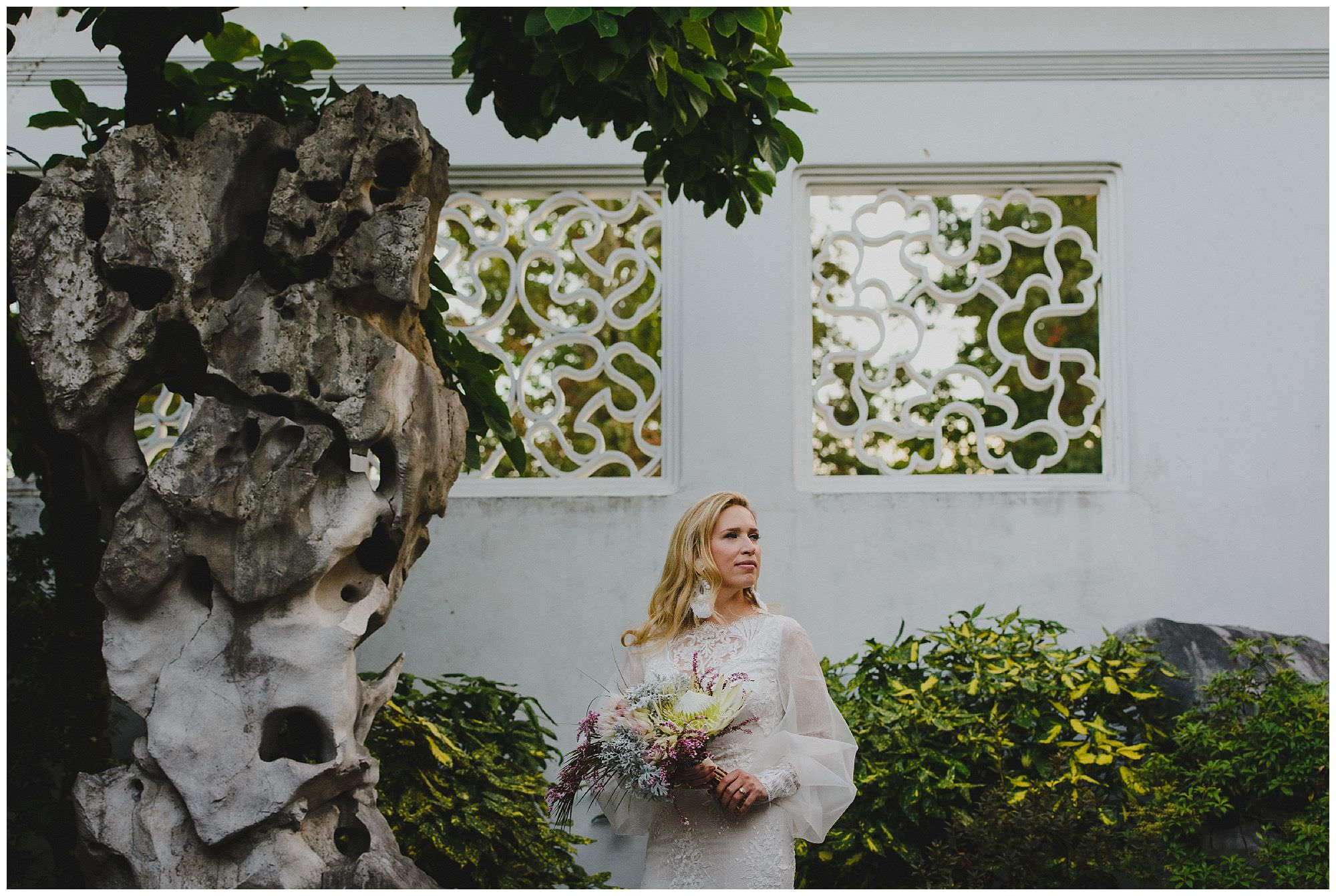 Bride in hand-made wedding dress with puffy sleeves at sunset at her wedding in Dr. Sun Yat-Sen Classical Chinese Gardens, Vancouver Wedding Photographer, bride holds a bouquet by the Bloom Room Botanical Gallery