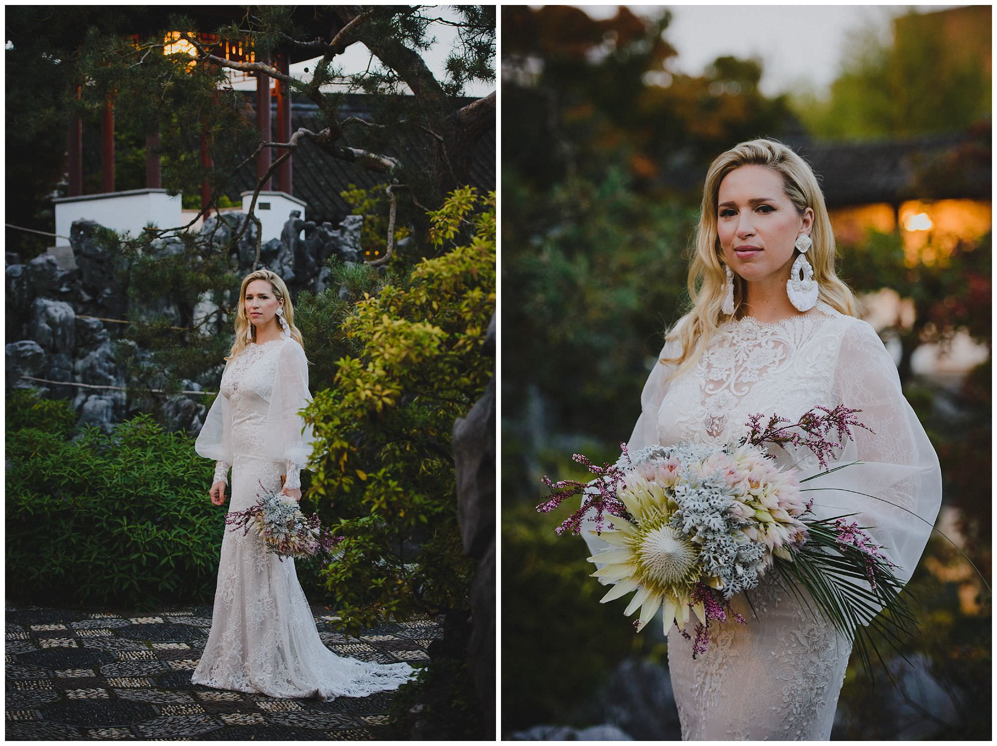 bride stands in Dr. Sun Yat-Sen Classical Chinese Gardens in Vancouver at sunset showing off her hand-made wedding dress, brides holds a bridal bouquet by the Bloom Room Botanical Gallery