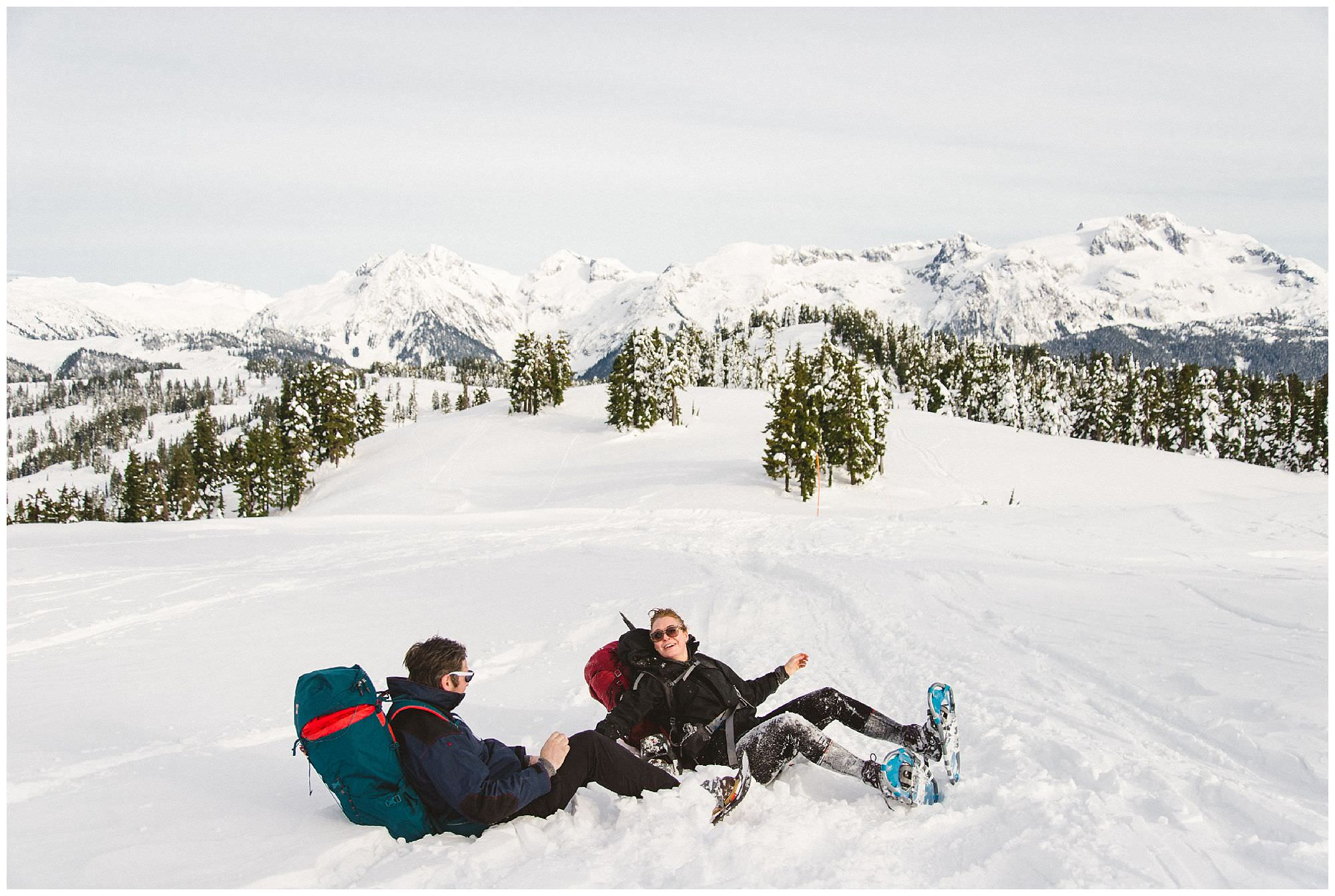 Two people falling in the snow while snowshoeing to Elfin Lakes in Garibaldi park, by travel photographer Ronnie Lee Hill Photography