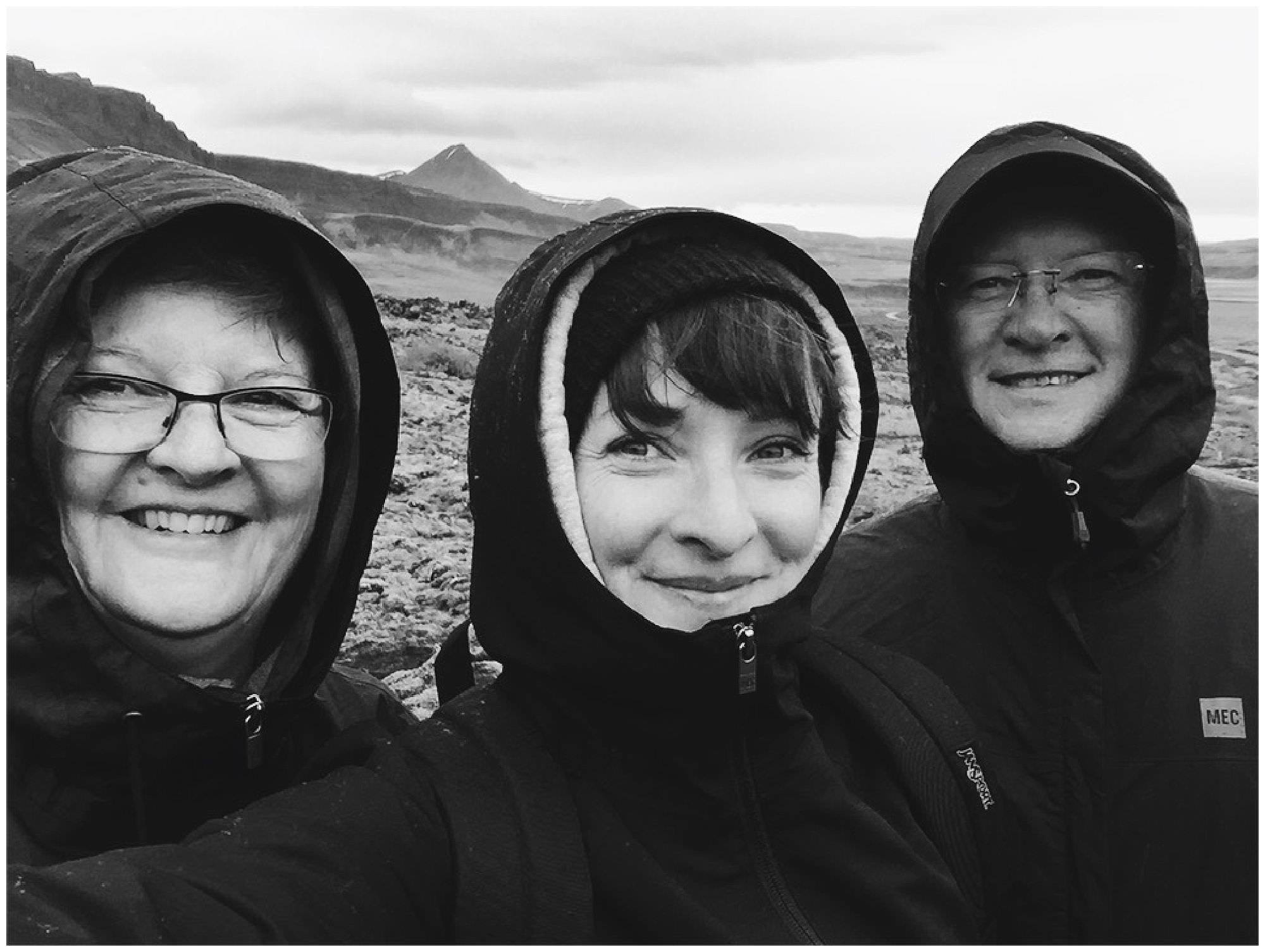 Destination wedding and travel photographer in selfie with parents in Iceland on top of volcano