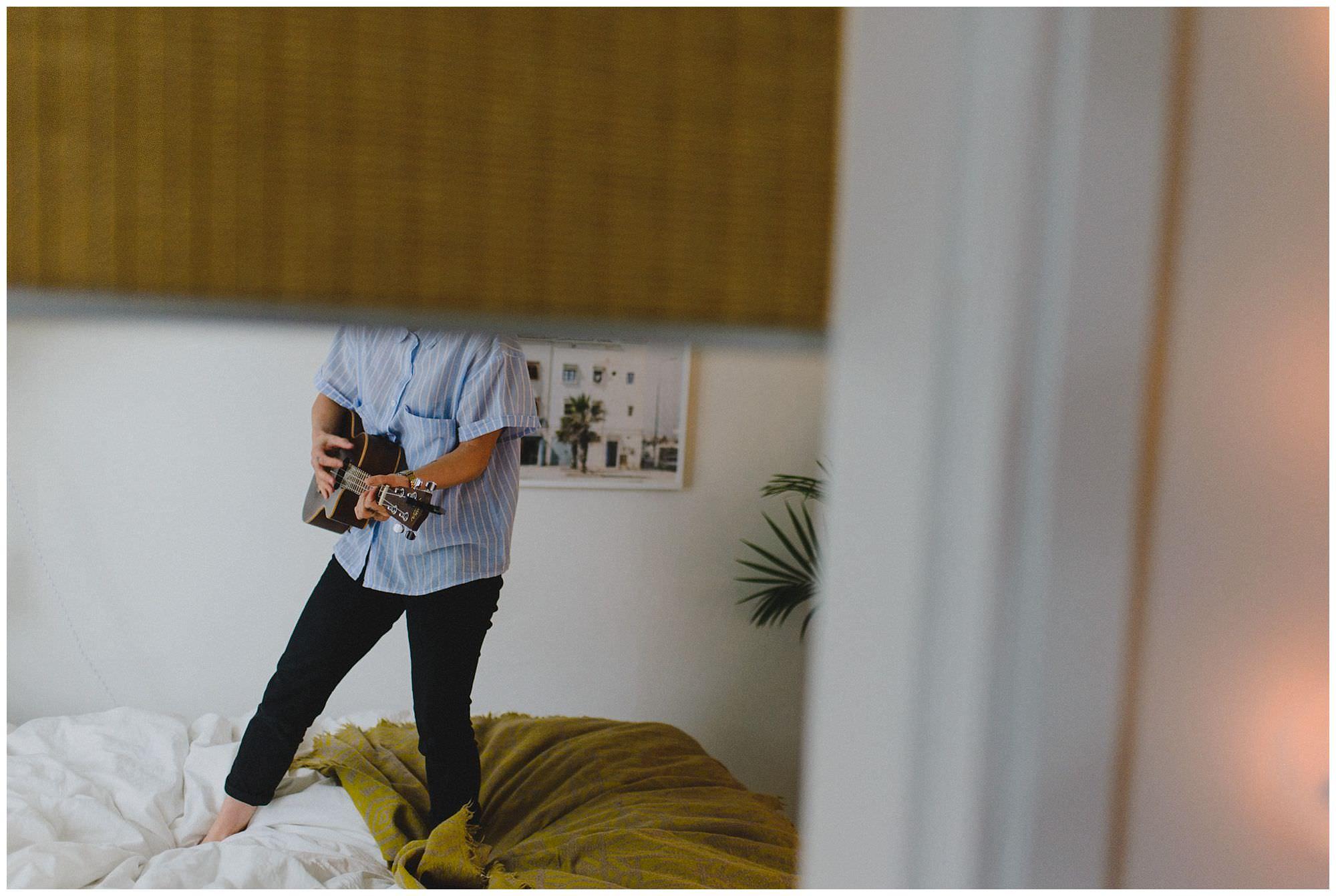 Musician Jody Mariko Okabe plays ukulele during in-home candid portrait photo session