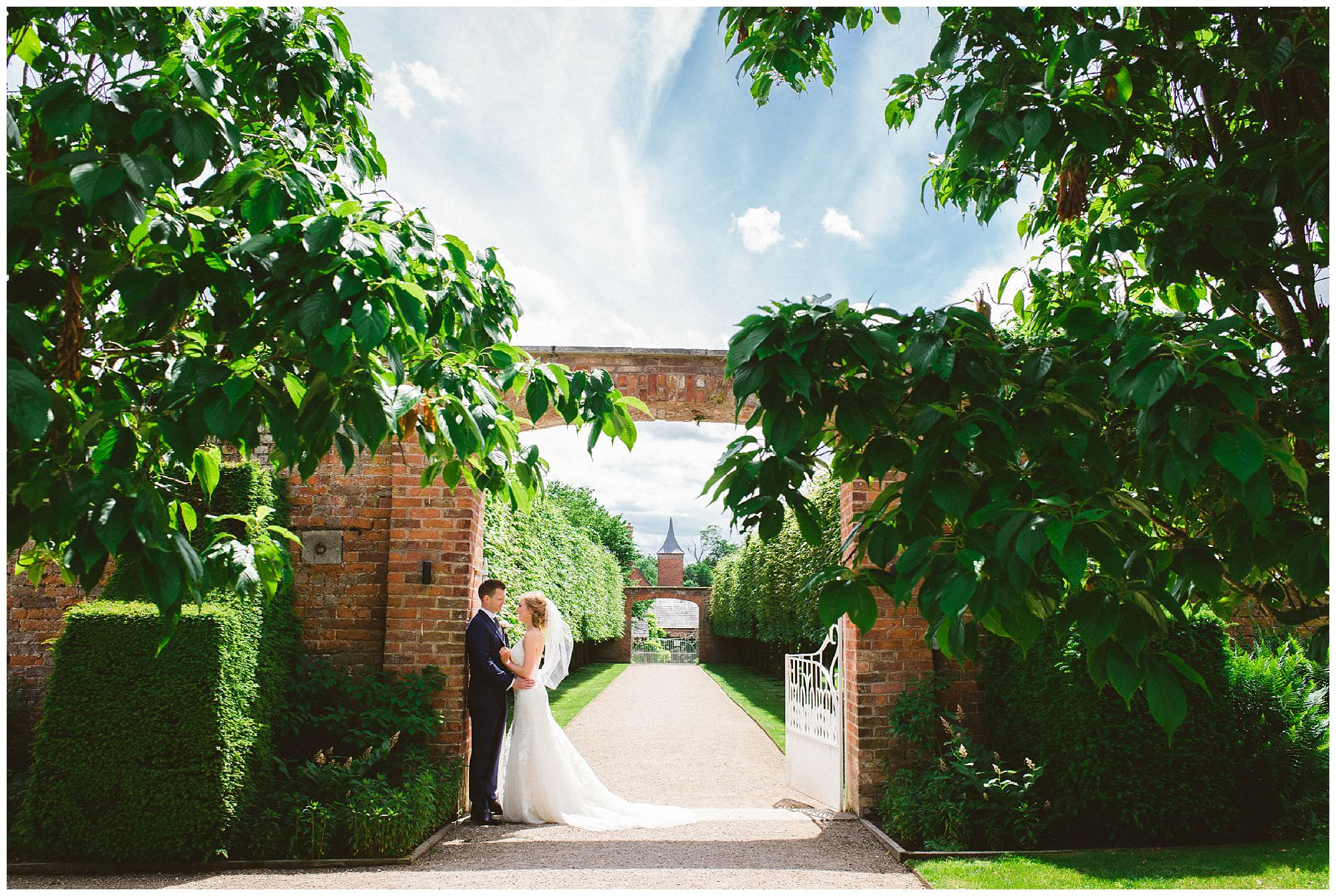 traditional portrait of bride and groom in gardens at Combermere Abbey in England by destination wedding photographer Ronnie Lee Hill Photography