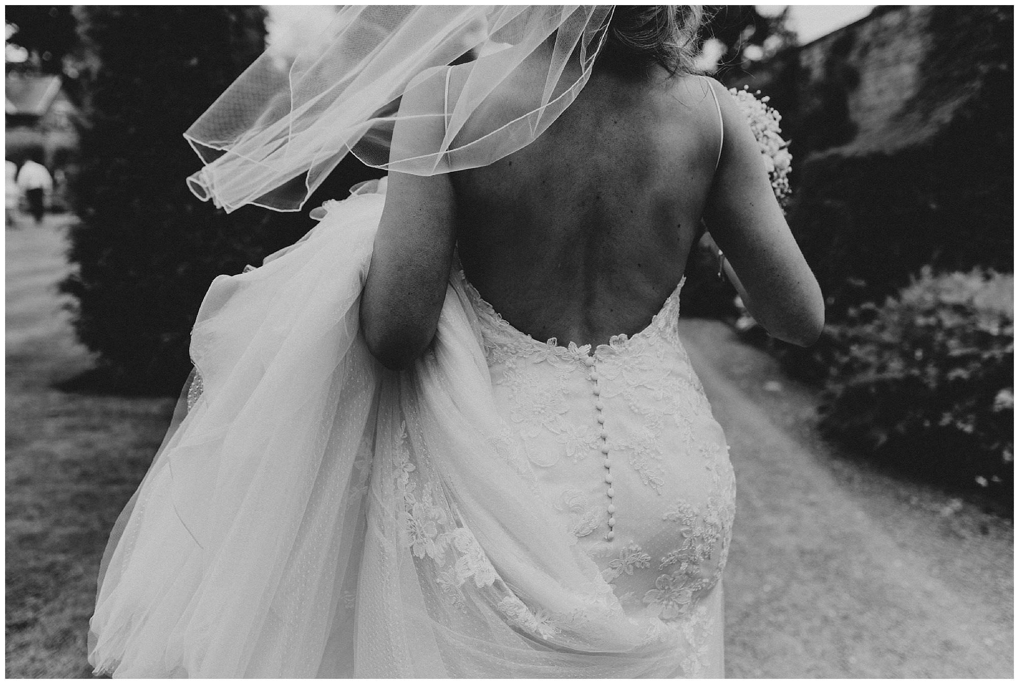 A brides bare back at her traditional English wedding at Combermere Abbey