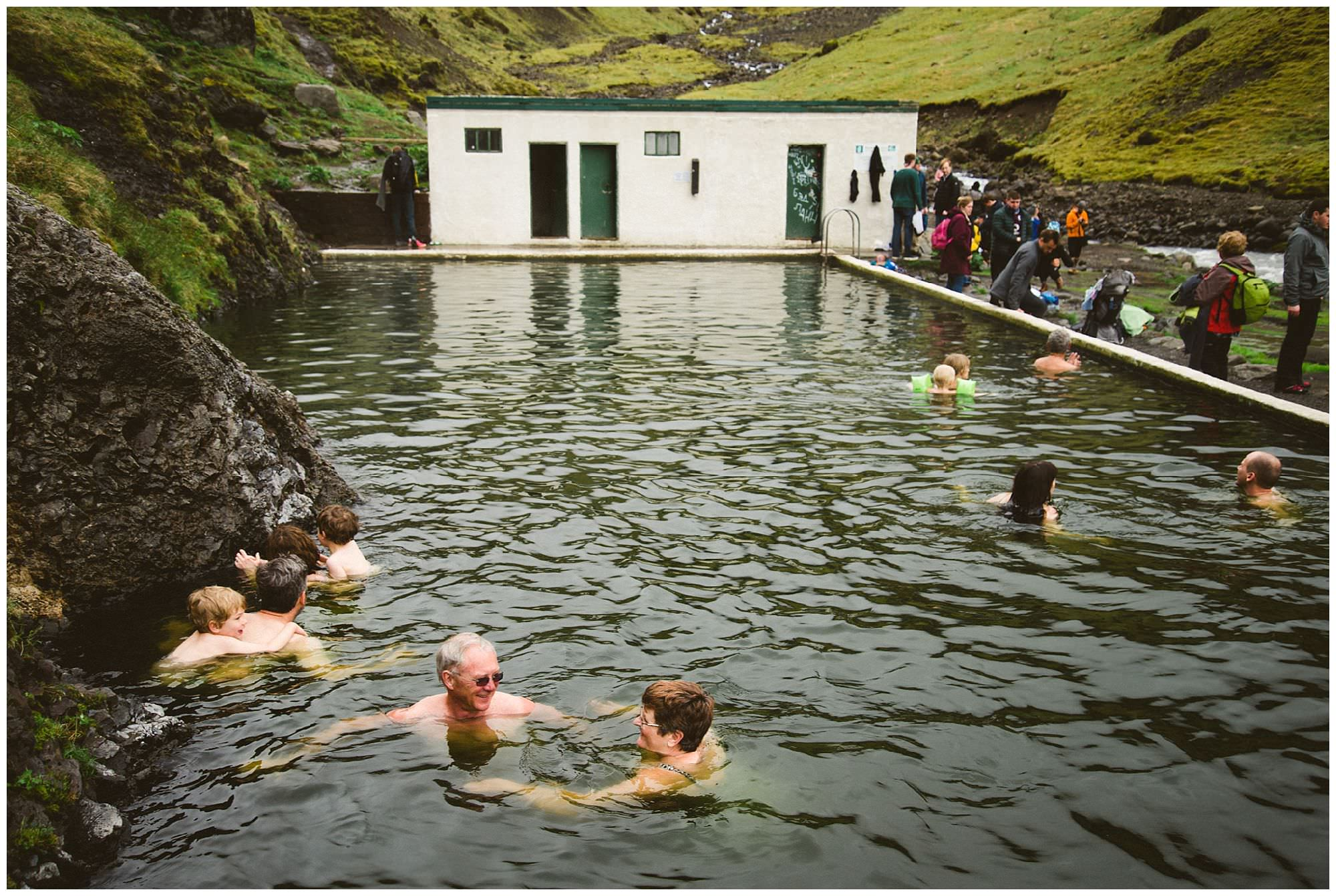 couple swims at natural hot spring in Iceland by adventure photographer Ronnie Lee Hill Photography, Iceland photographer