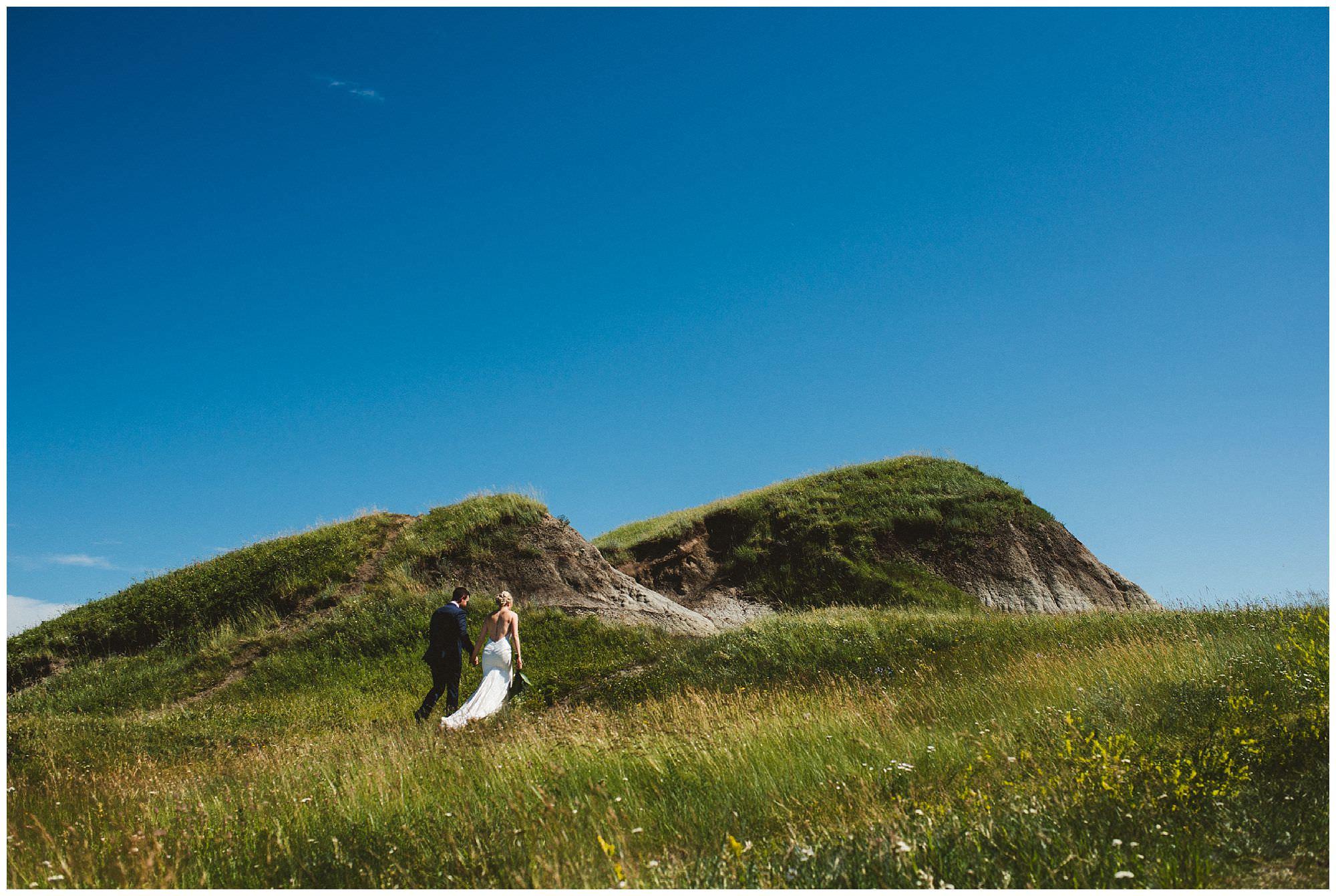 Bride and groom walk through epic scenery at Kleskun Hills in Grande Prairie Alberta, destination wedding photographer