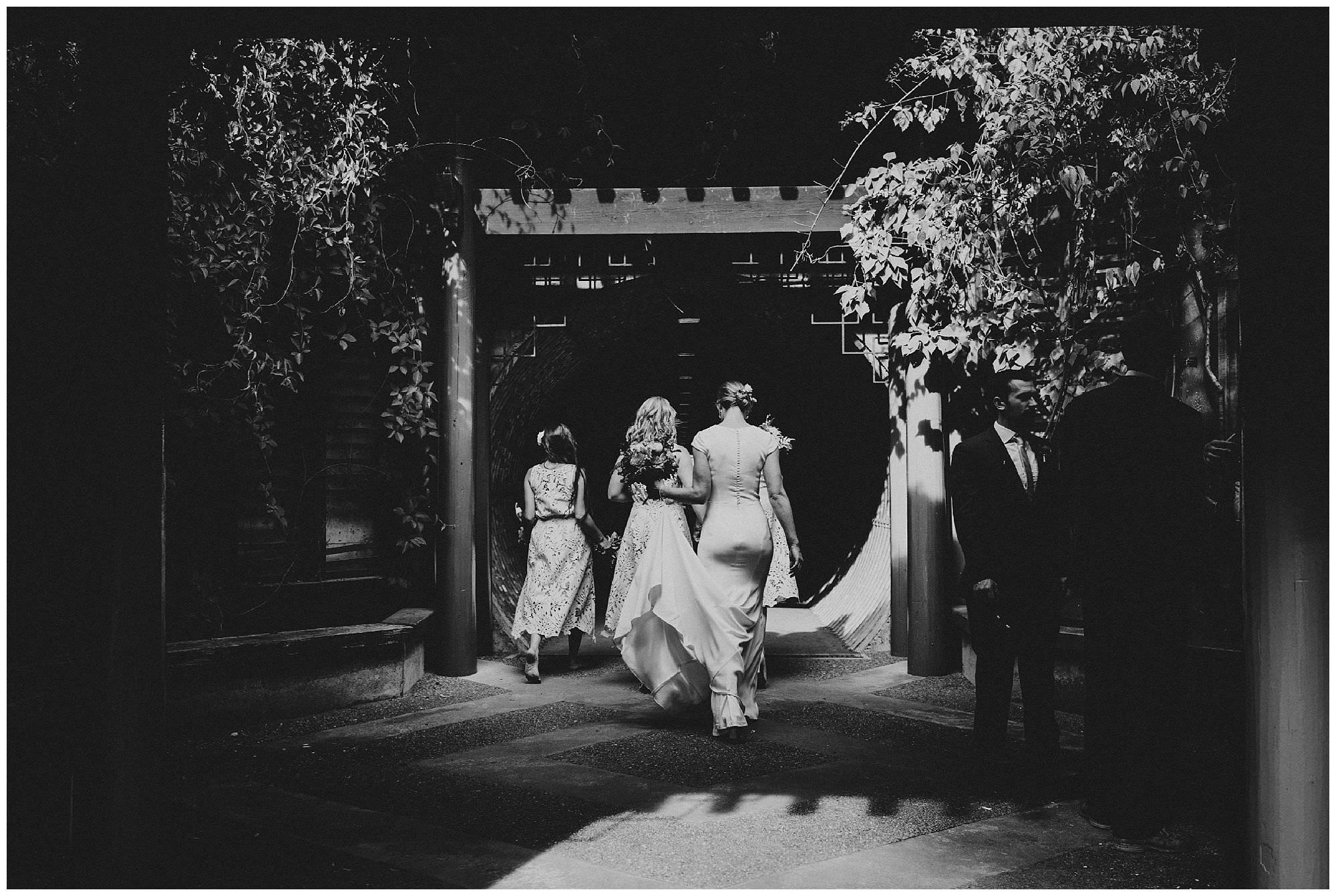 Candid moment of bride and bridesmaids walking through UBC Botanical Gardens by Vancouver wedding photographer Ronnie Lee Hill Photography