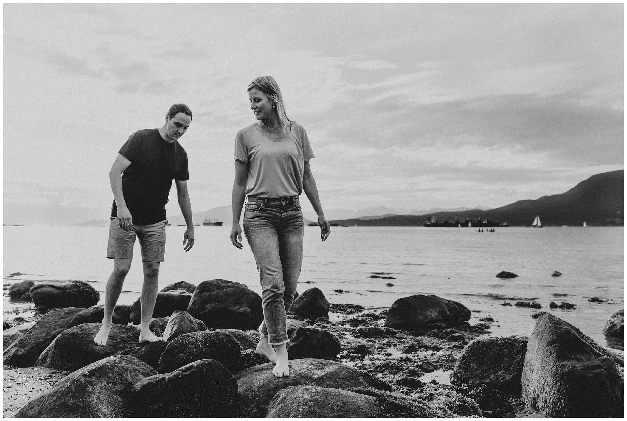 a candid sunset engagement session at Jericho Beach, couple walking on rocks