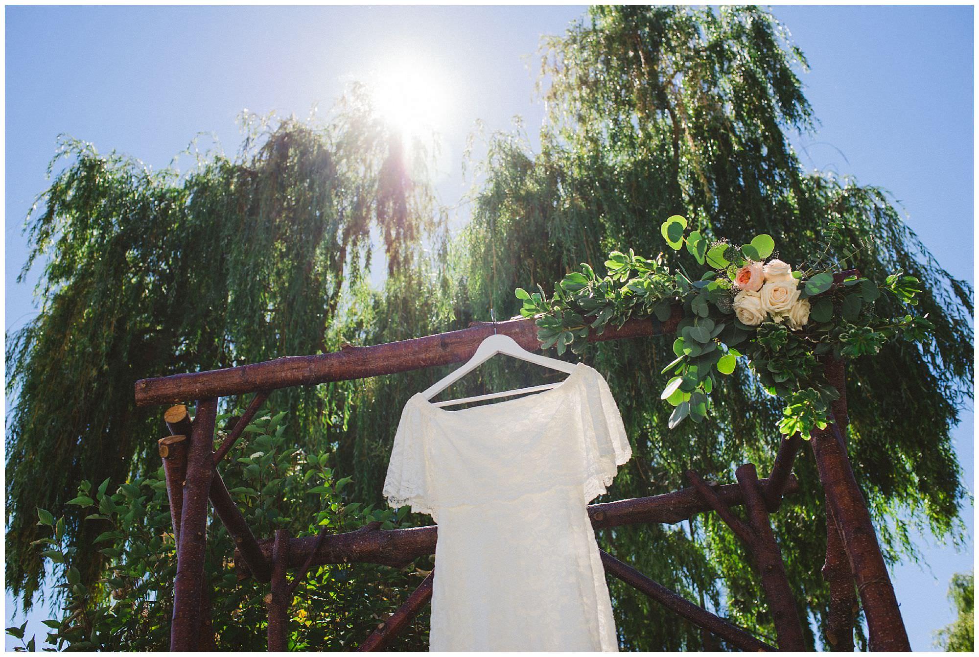 Boho wedding dress hangs in sun before intimate backyard wedding in Kelowna BC