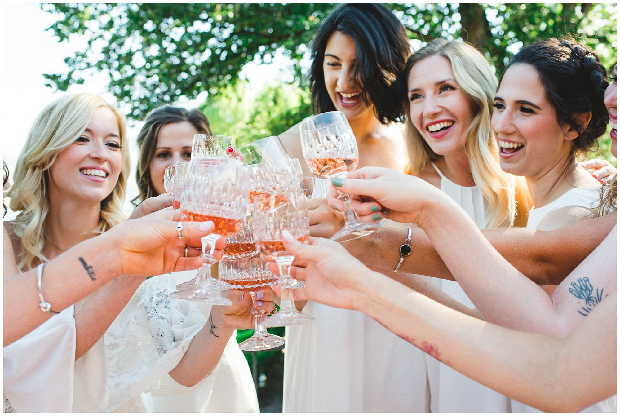 Bridesmaids cheers with champagne before ceremony, backyard beach wedding in Kelowna BC, candid documentary wedding photography