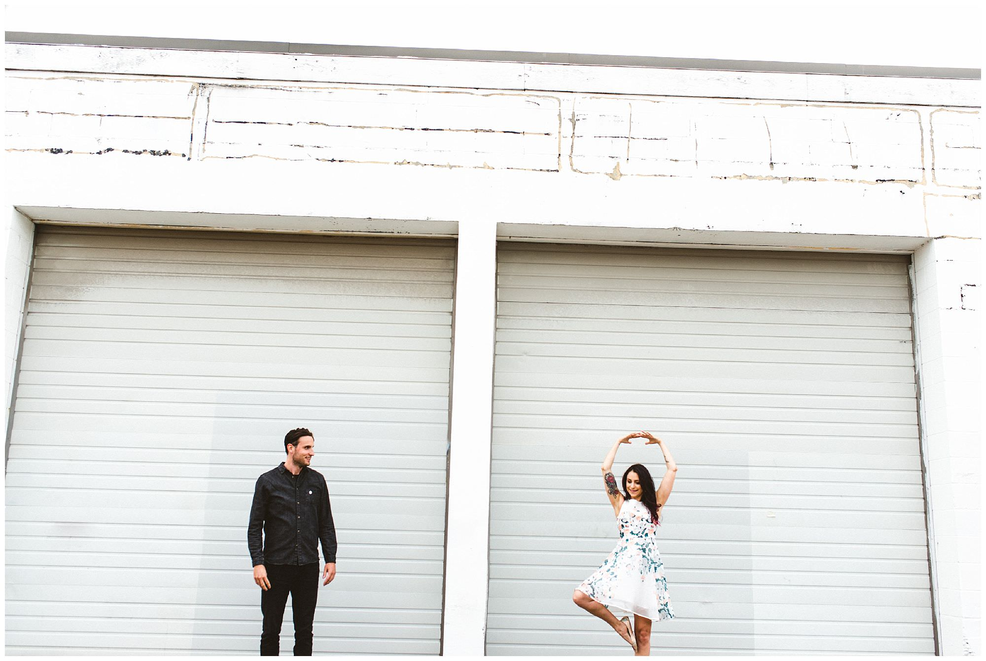 Woman with tattoos dances during engagement session in East Vancouver, candid engagement photography