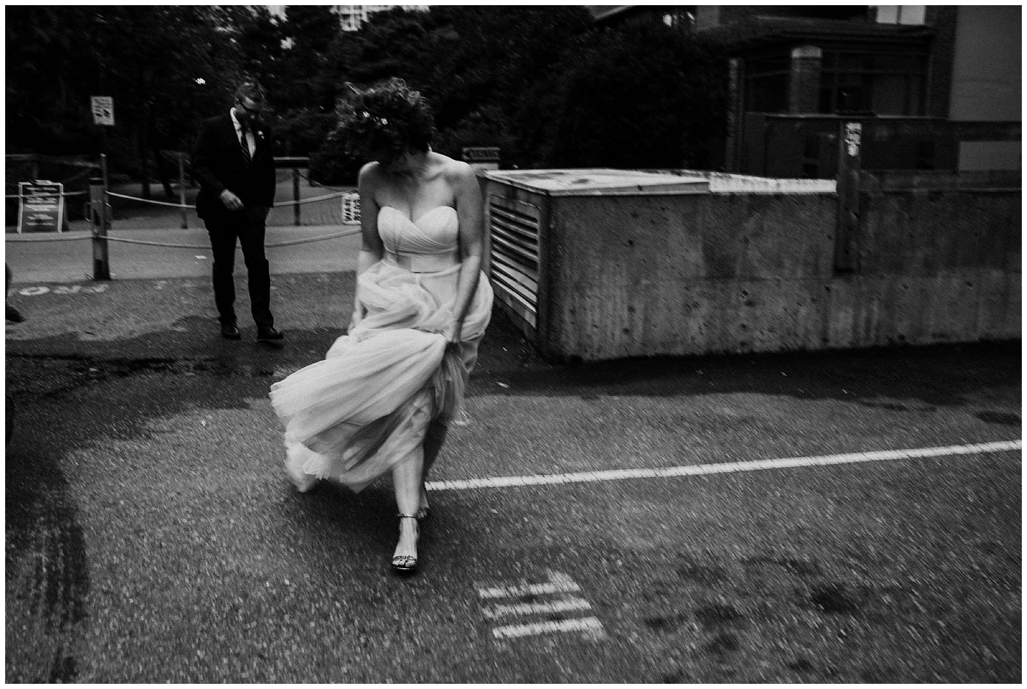 Vancouver bride runs through Yaletown parking lot to her wedding reception at The Loft at Earls, captured by candid documentary wedding photographer Ronnie Lee Hill