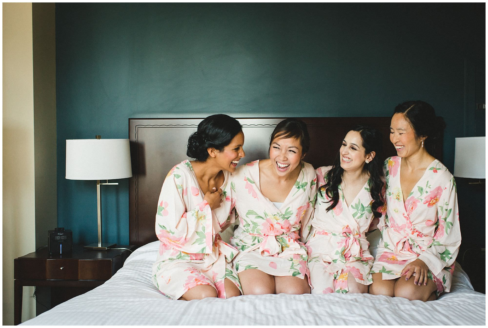 Chinese bride and bridesmaids laugh on bed wearing matching robes at Pan Pacific Hotel in Vancouver by candid wedding photographer Ronnie Lee Hill Photography