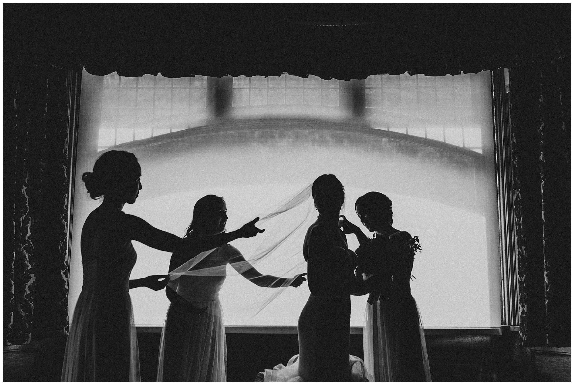 Silhouette of bride and bridesmaids getting ready in Vancouver at Cecil Green Park House wedding, candid moment