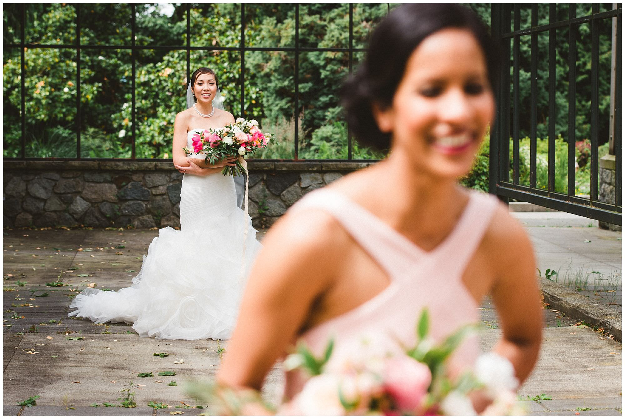 Candid photo of bride and bridesmaid in greenhouse at UBC Cecil Green Park house wedding