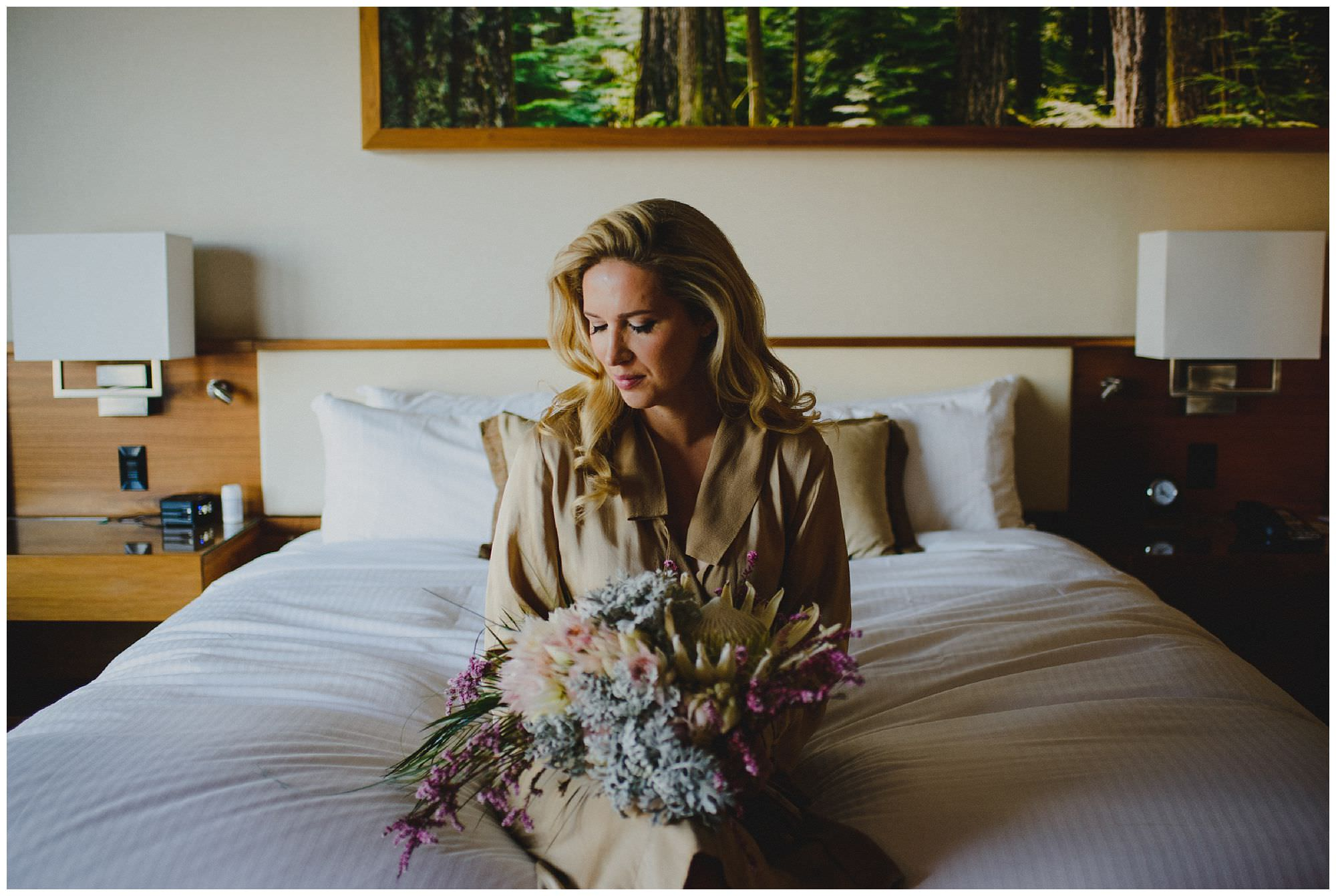 Bride getting ready, sitting on bed in gold robe at Pan Pacific Hotel in Vancouver BC by candid wedding photographer