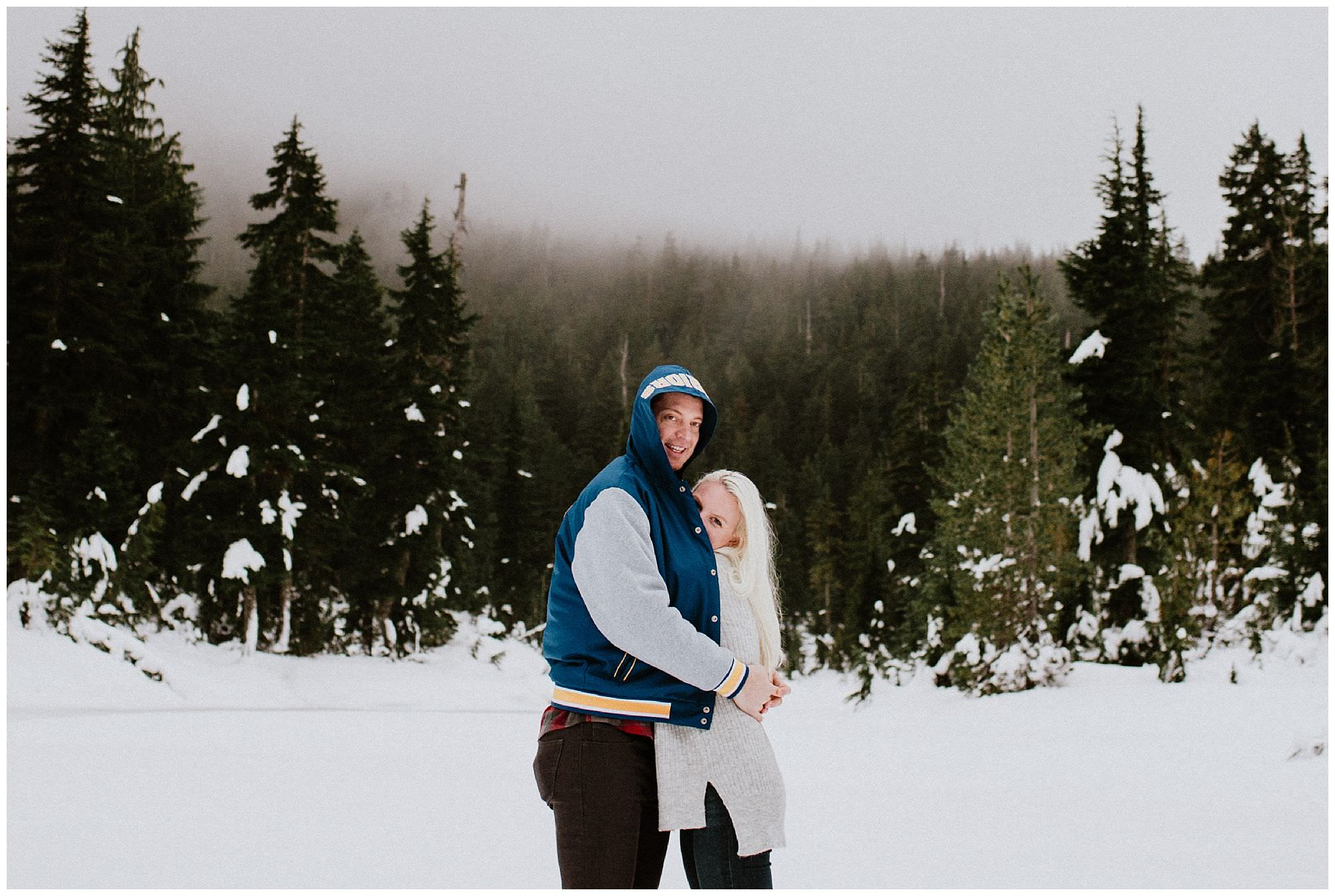 A couple keeps warm during a snowy mountain engagement session on Cypress Mountain