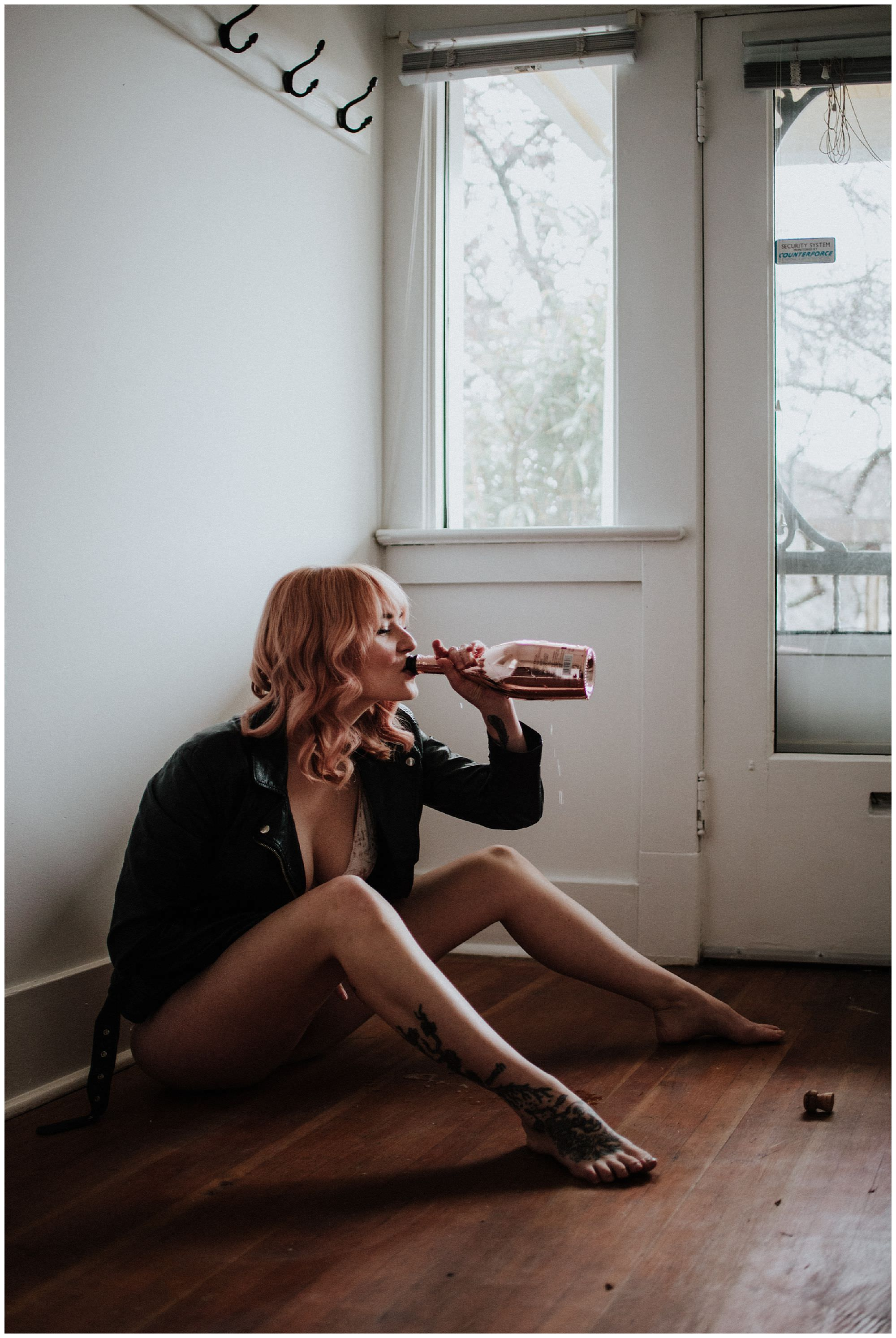 Singer of Vancouver band Youngblood drinks pink champagne during in-home boudoir portrait session with Vancouver photographer Ronnie Lee Hill Photography