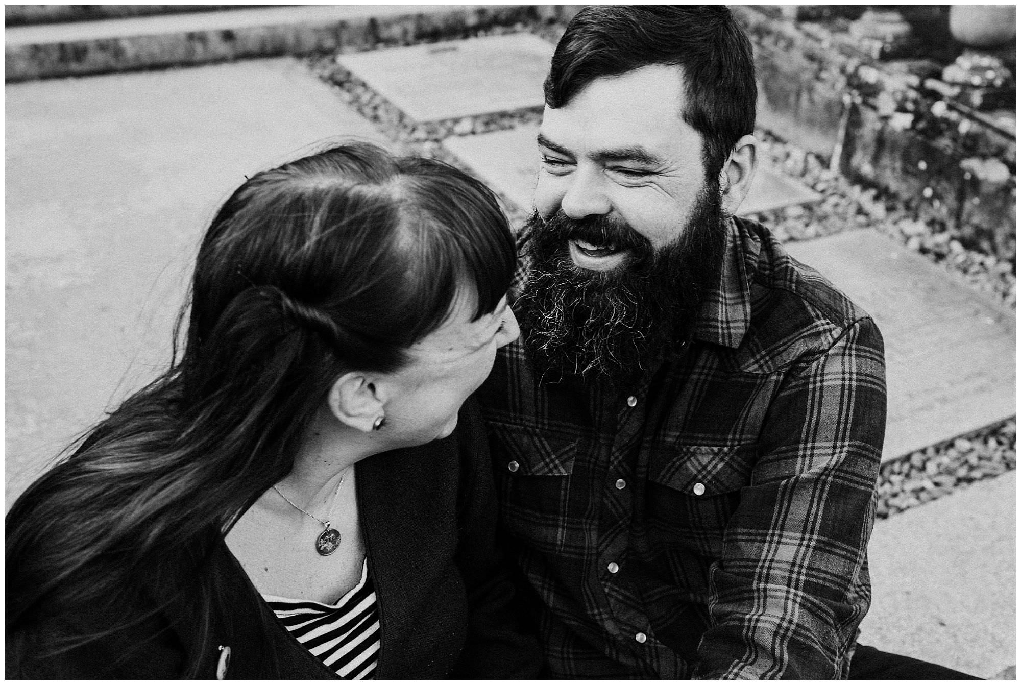 bearded-man-laughing-on-stairs-engagement-photography-at-royal-roads-university-victoria