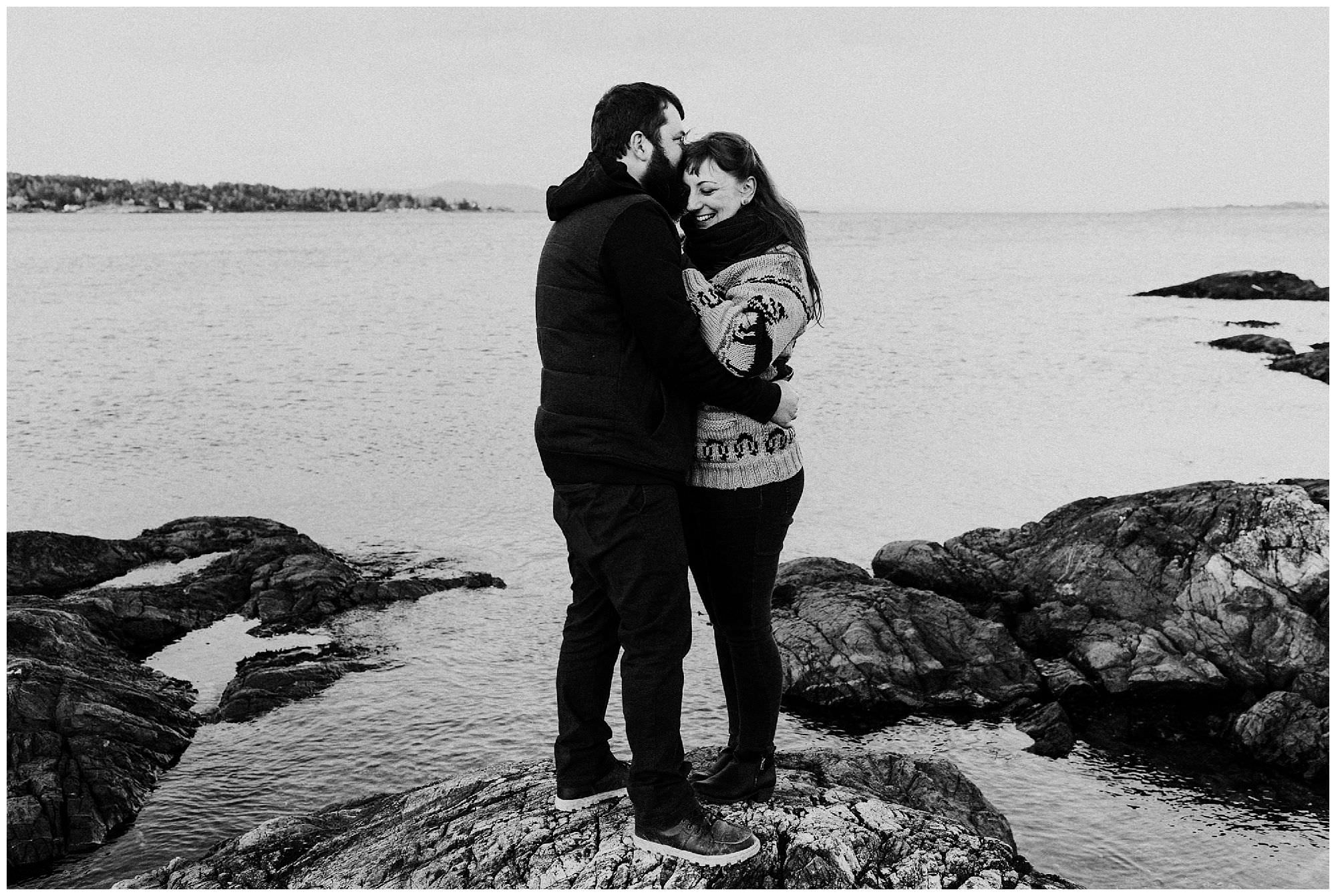 black-and-white-engagement-photography-at-cattle-point-victoria-couple-hugging-on-rocks