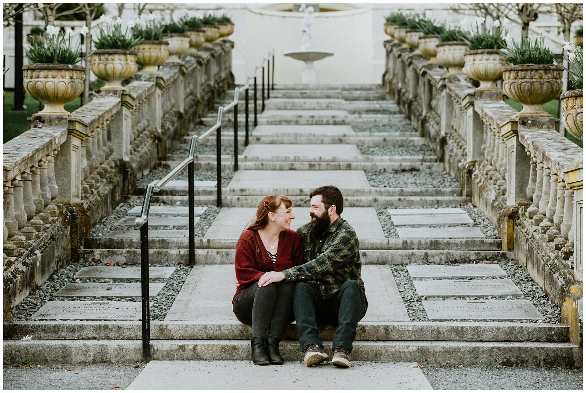 couple-cuddling-on-stairs-engagement-photography-at-royal-roads-university-victoria-bc