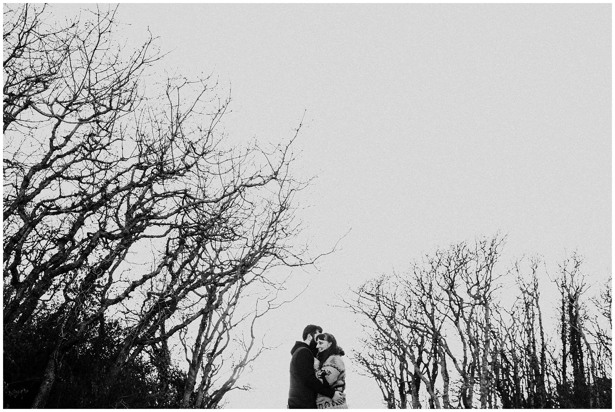 couple-hugging-bare-trees-black-and-white-sunset-engagement-photography-at-cattle-point-victoria-bc