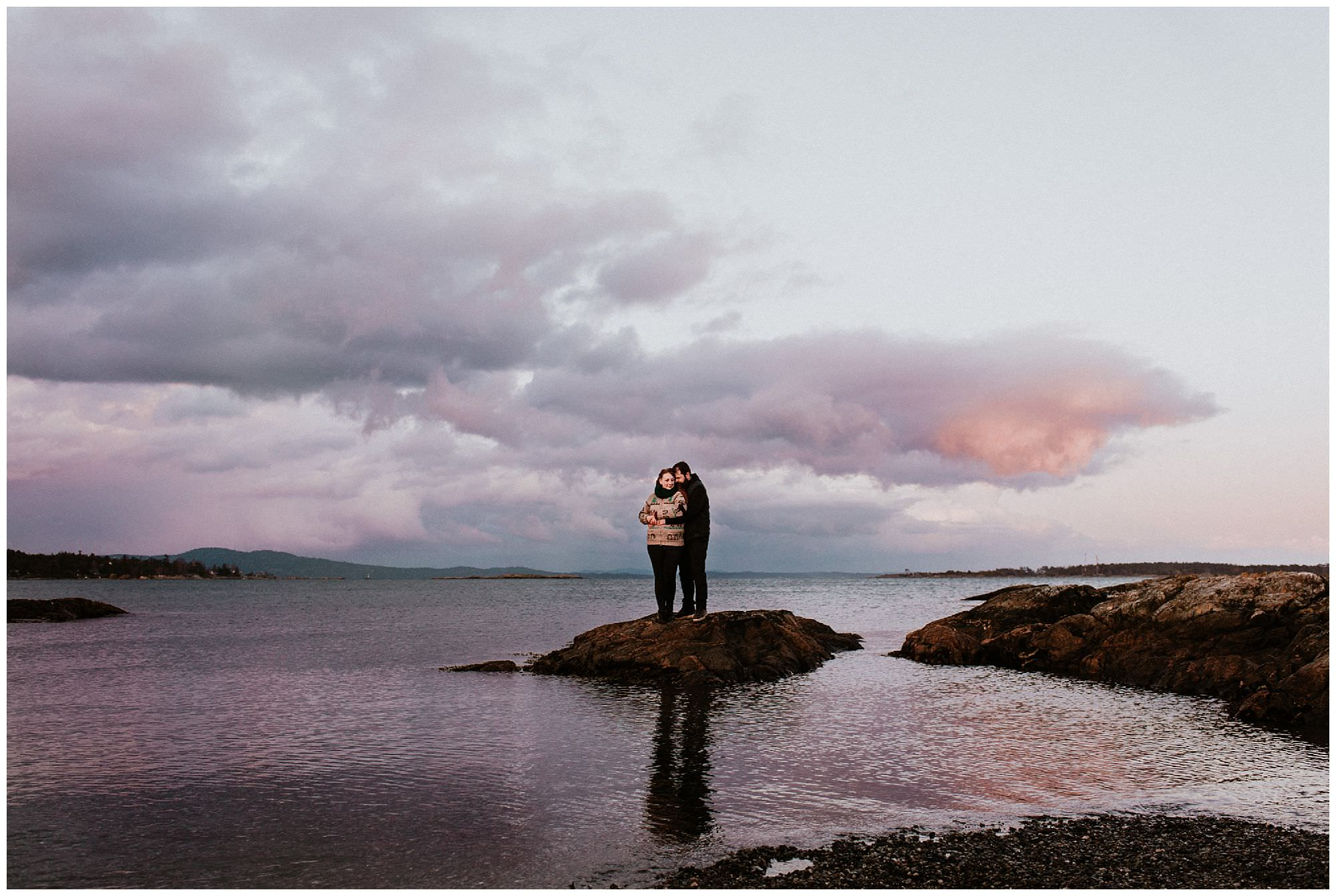 couple-hugging-pink-purple-sunset-engagement-photography-at-cattle-point-victoria-bc