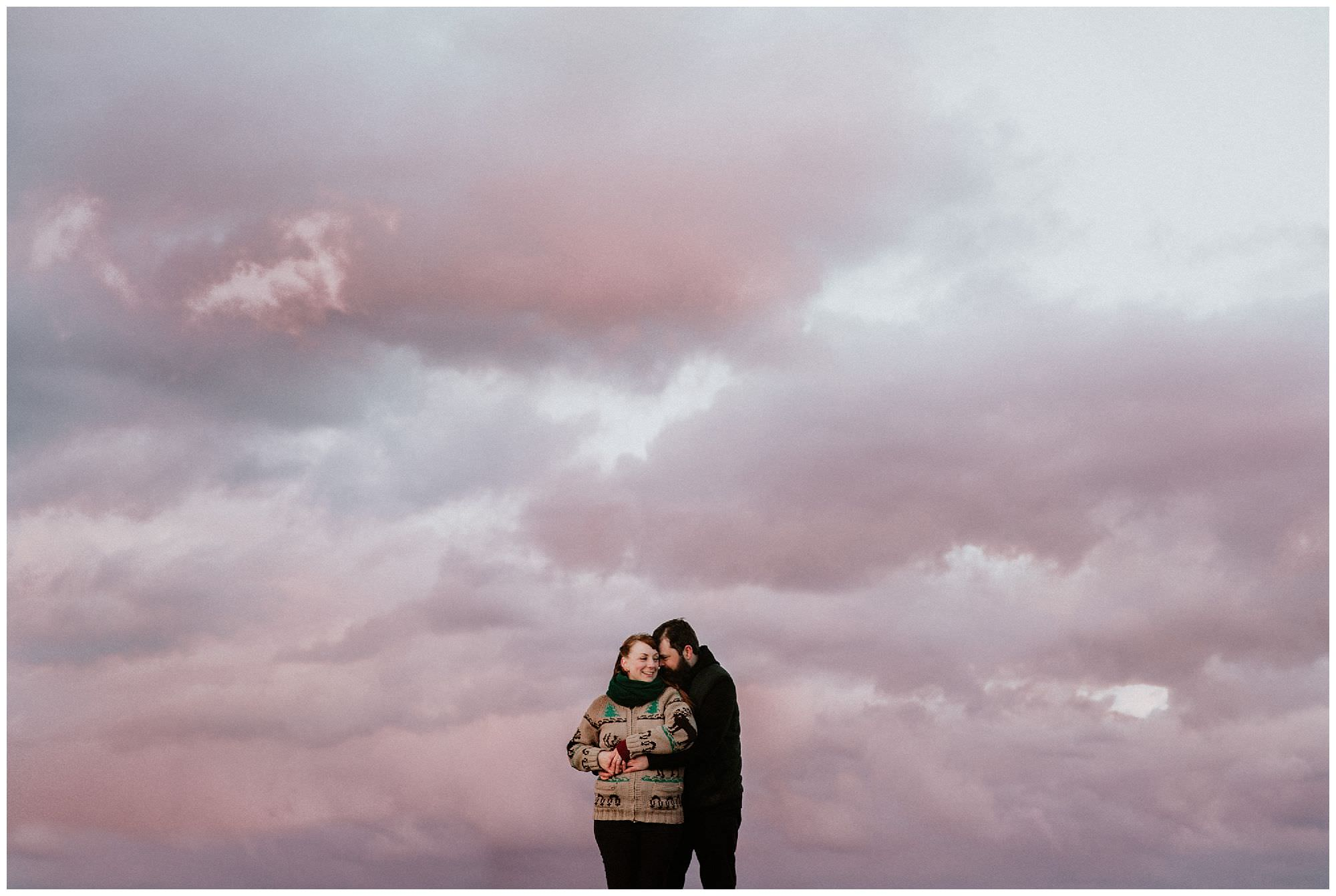 couple-hugging-pink-sunset-engagement-photography-at-cattle-point-victoria-bc