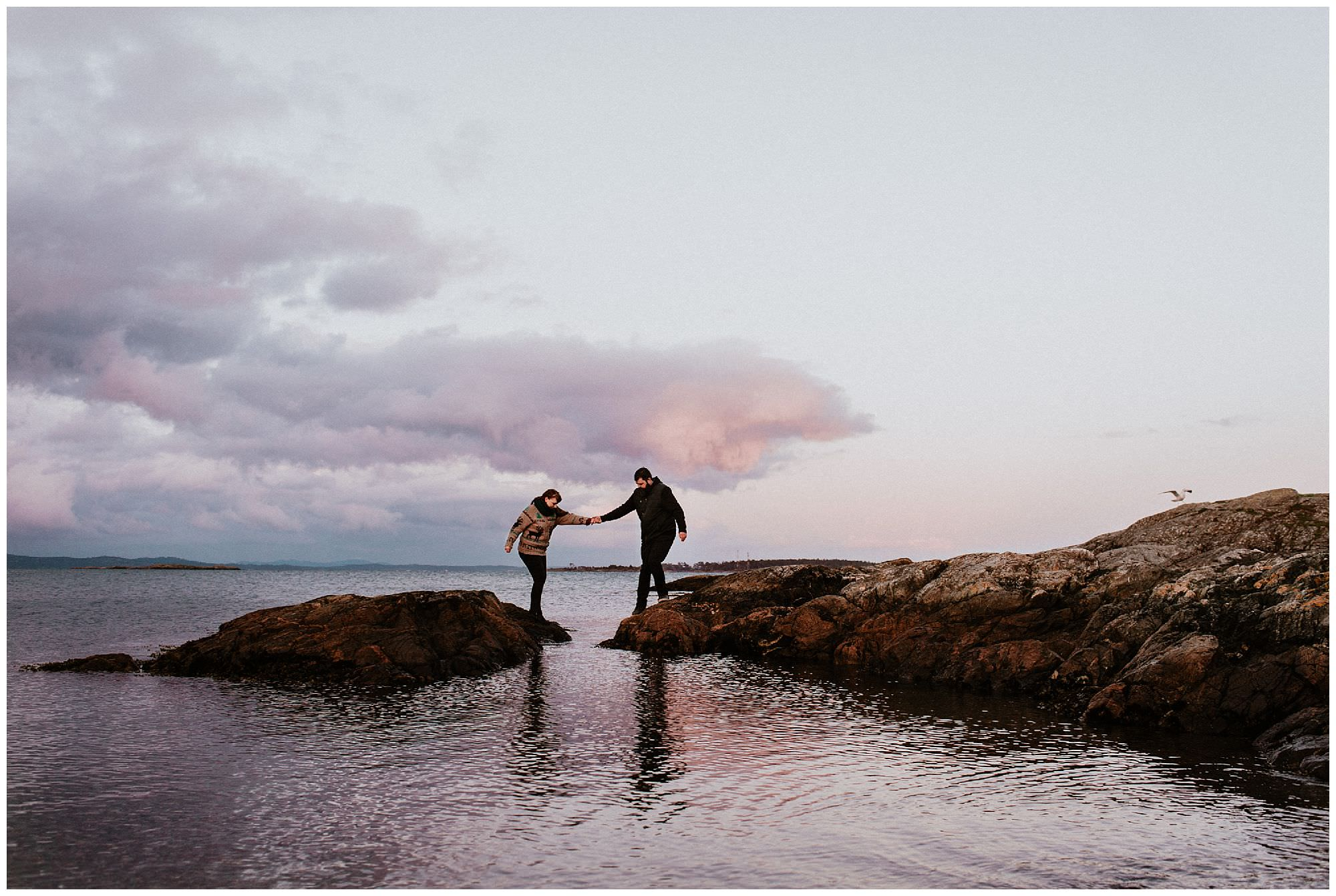 couple-jumping-rocks-pink-sunset-engagement-photography-at-cattle-point-victoria-bc