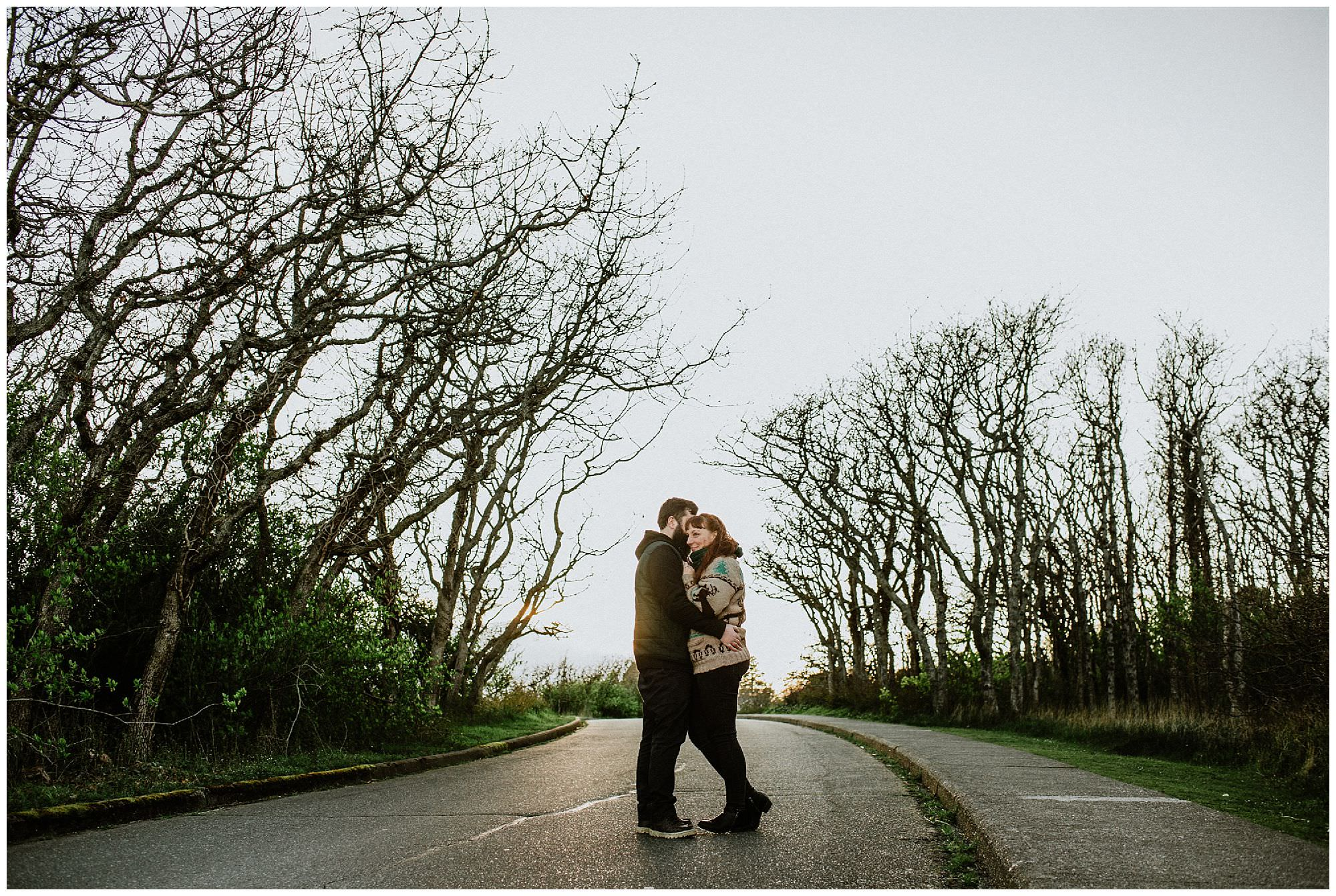 couple-standing-in-road-spring-sunset-engagement-photography-at-cattle-point-victoria-bc