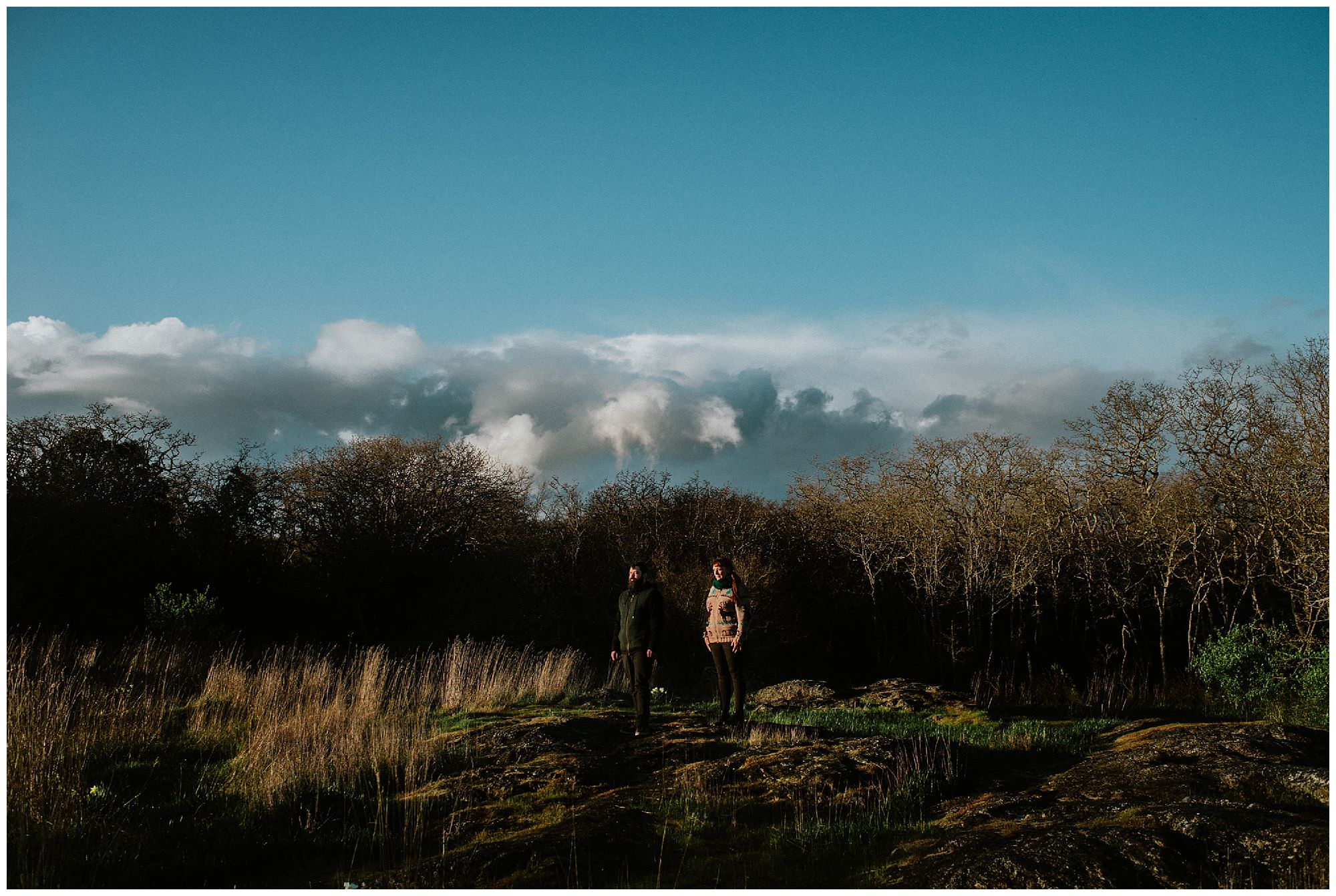 couple-standing-in-sunshine-during-stormy-sunset-engagement-session-at-cattle-point-victoria-bc