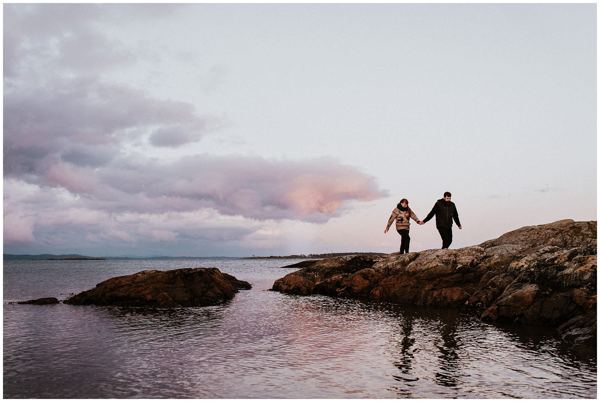 couple-walking-on-rocks-during-pink-sunset-engagement-photography-at-cattle-point-victoria-bc