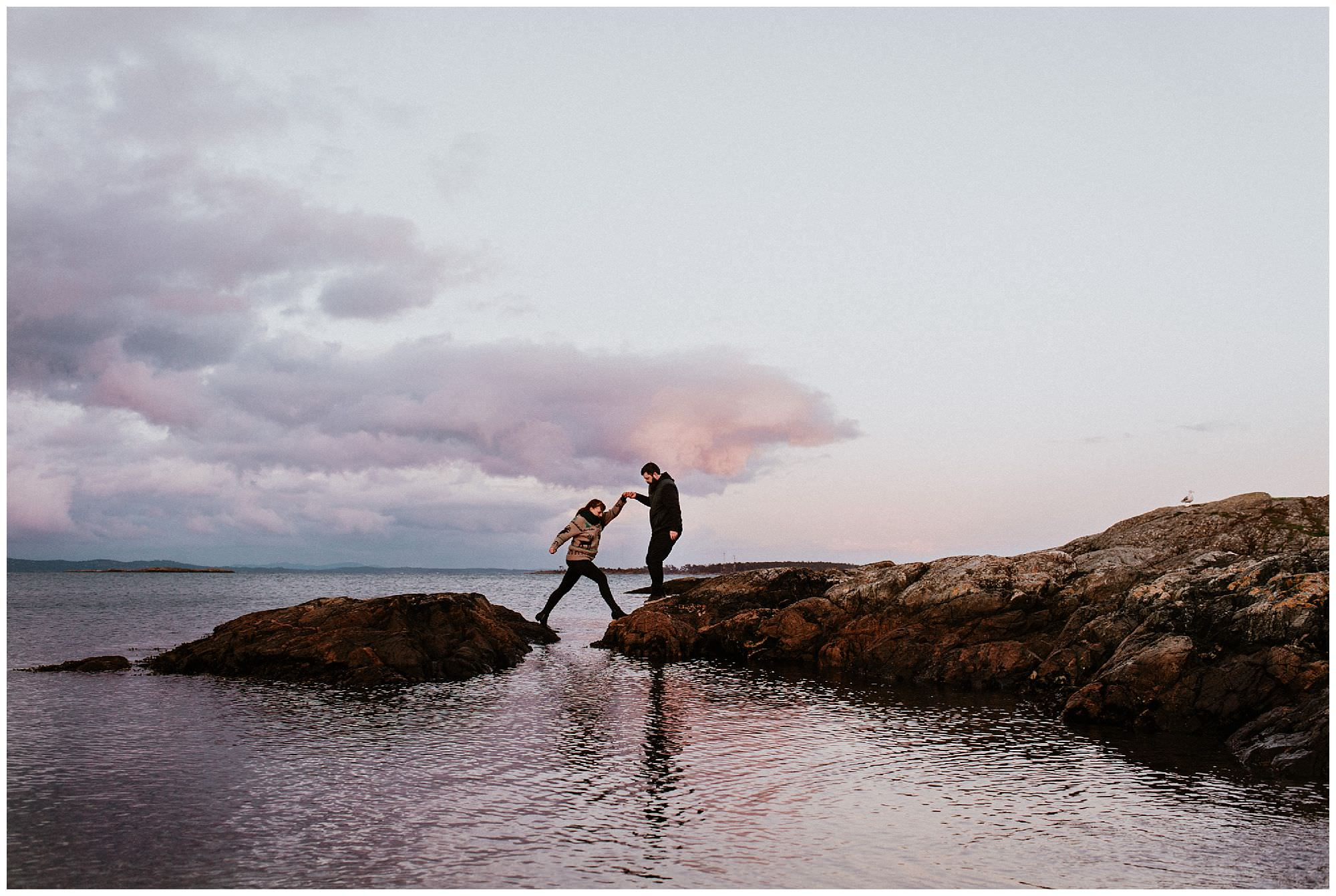 man-helping-woman-jump-rocks-pink-sunset-engagement-photography-at-cattle-point-victoria-bc