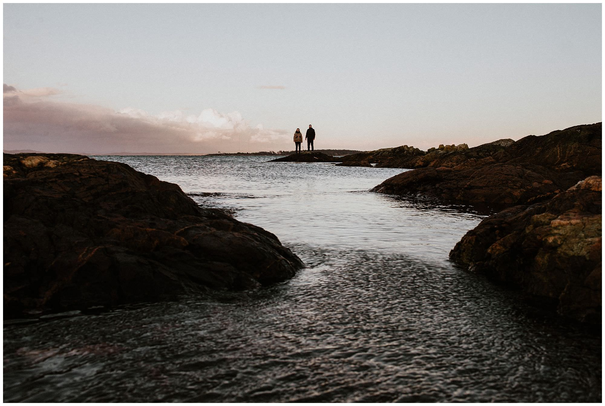 sunset-landscape-engagement-session-couple-standing-on-rocks-at-cattle-point-victoria-bc
