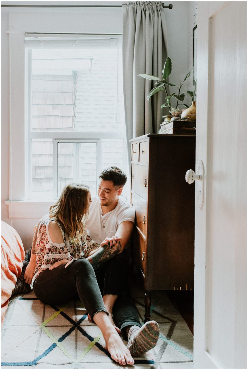 couple laughing on bedroom floor near Main Street in Vancouver