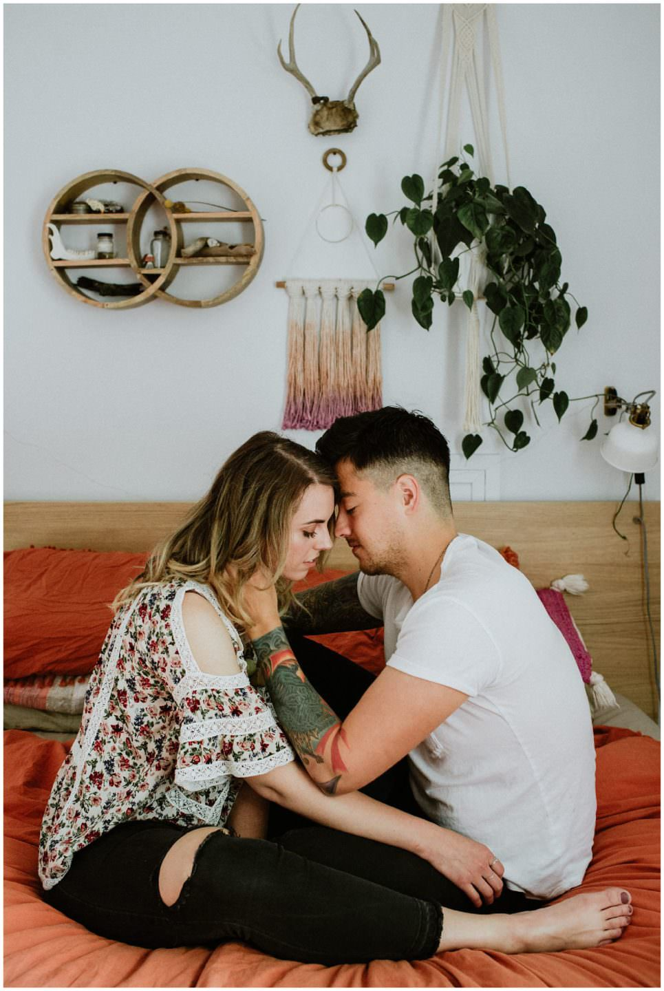 tattooed couple cuddling in vintage bedroom Vancouver