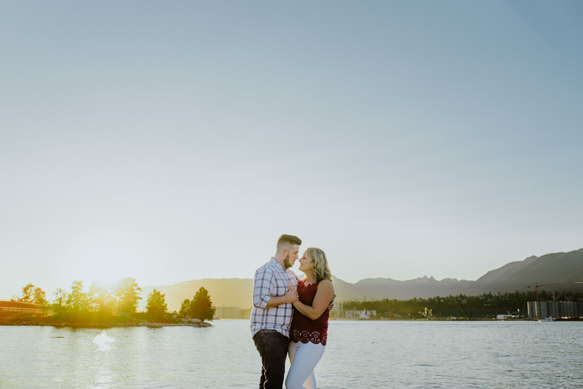 couple cuddling at sunset with mountain views at New Brighton Beach Vancouver engagement session