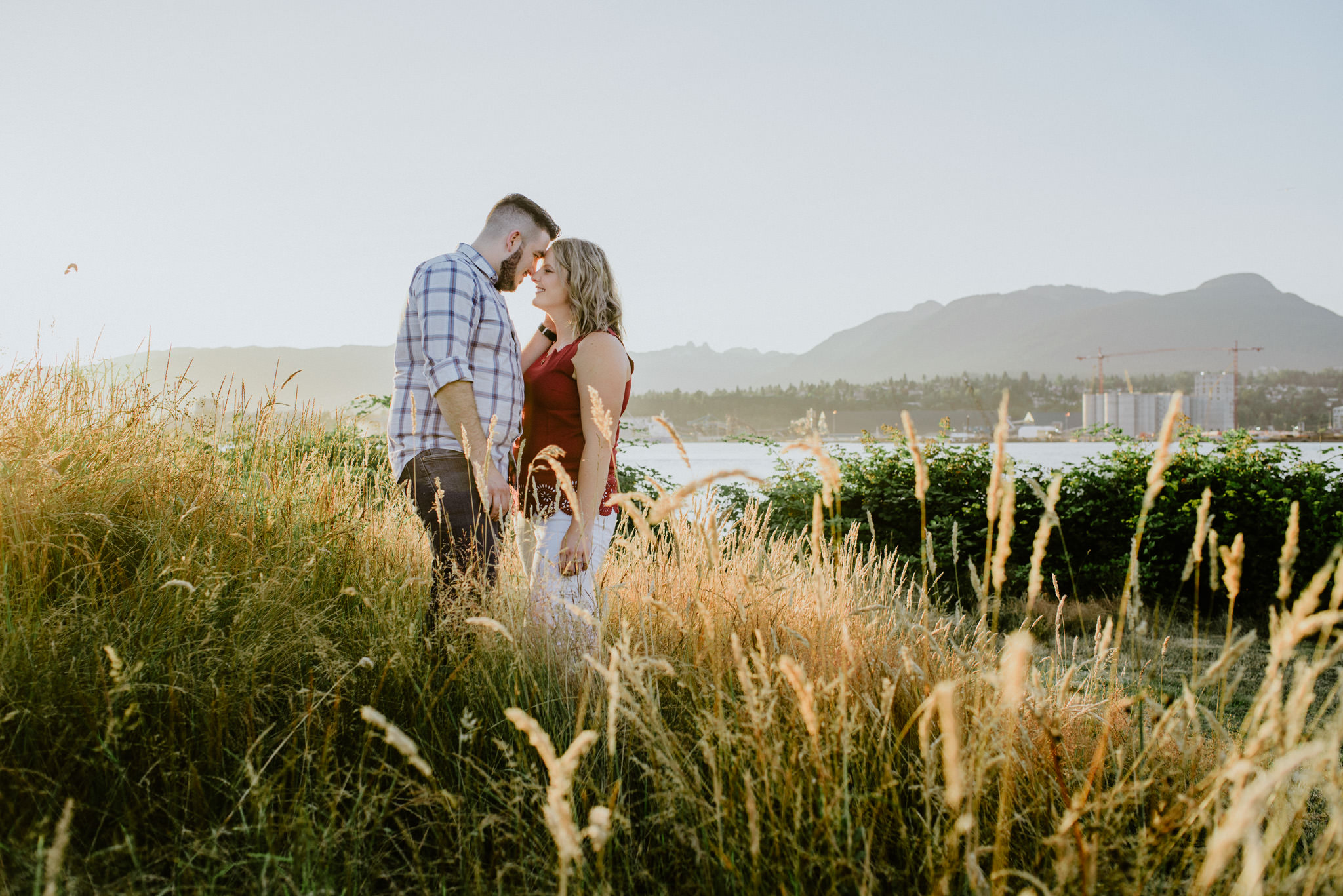couple nuzzling in long grass at sunset New Brighton Beach engagement Vancouver