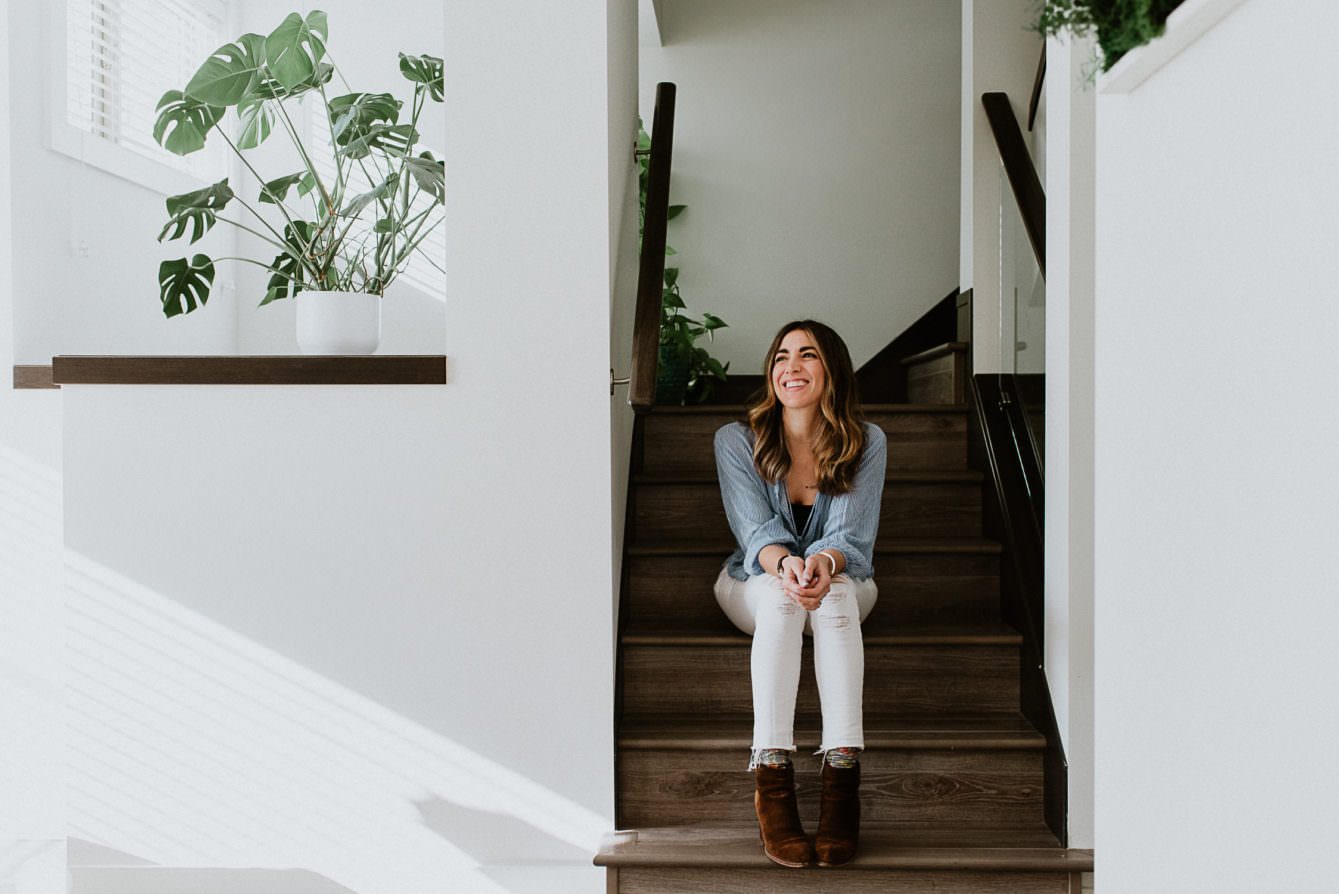 portrait of pretty woman sitting on stairs in airy home by Vancouver portrait photographer Ronnie Lee Hill